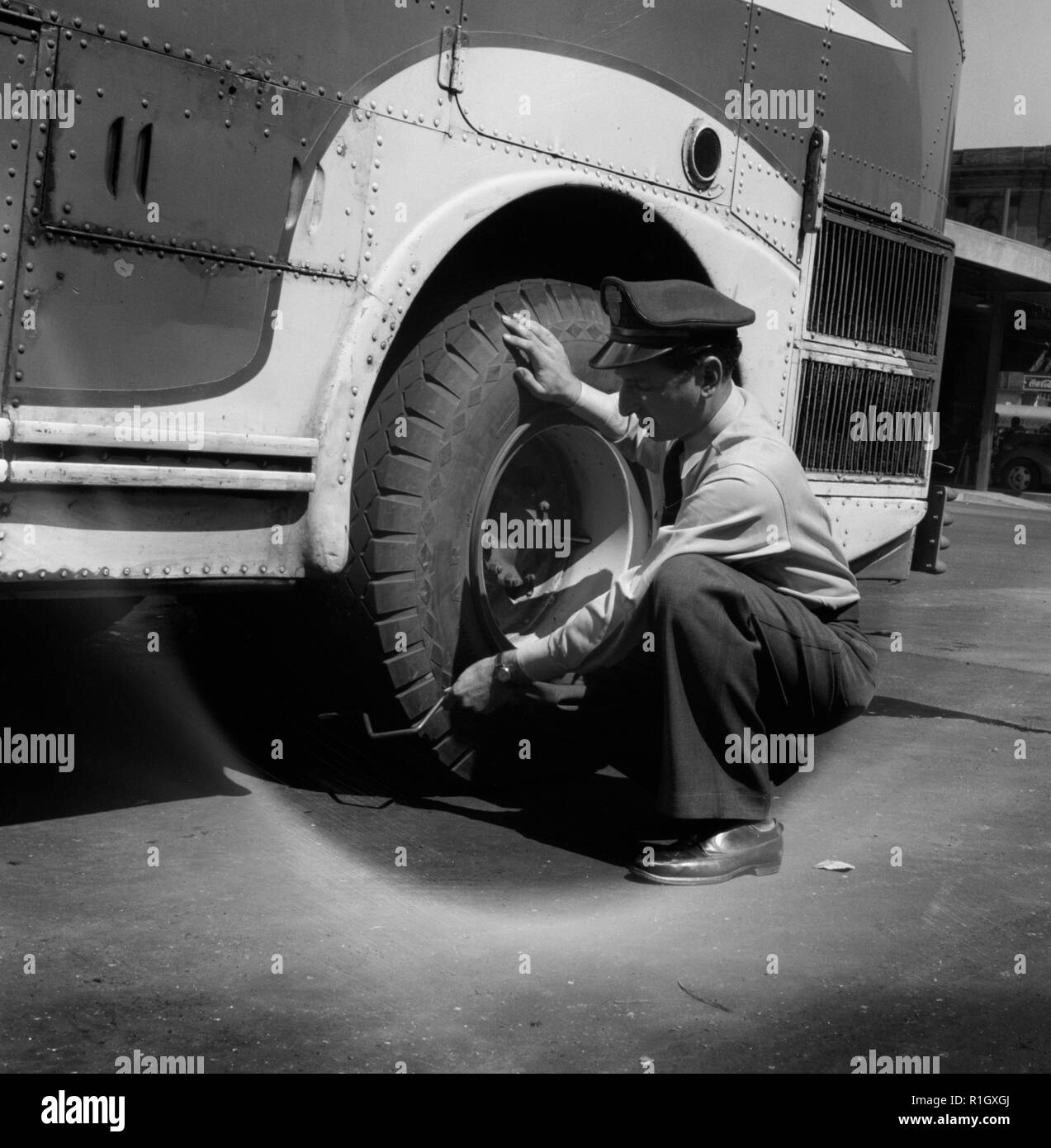 Columbus, Ohio. Randy Pribble, a bus driver for the Pennsylvania Greyhound Lines, Incorporated, checking tires on a bus by thumping them before taking it out on a run. Since there are two tires on the back, the sound is the best way of telling if one of them is flat. September 1943 Stock Photo
