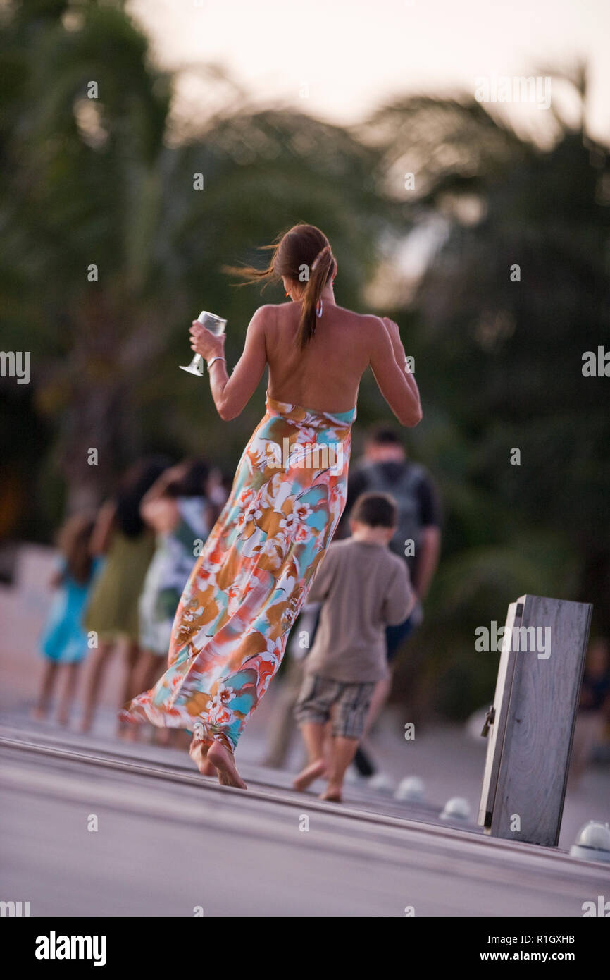 Barefoot young woman dancing along a jetty while carrying a glass of wine. - Stock Image