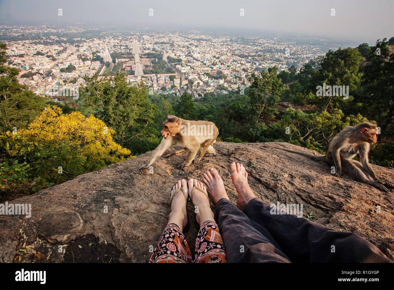 Couple legs sitting at Arunachala mountain view, Tiruvannamalai, Tamil Nadu, India - Stock Image