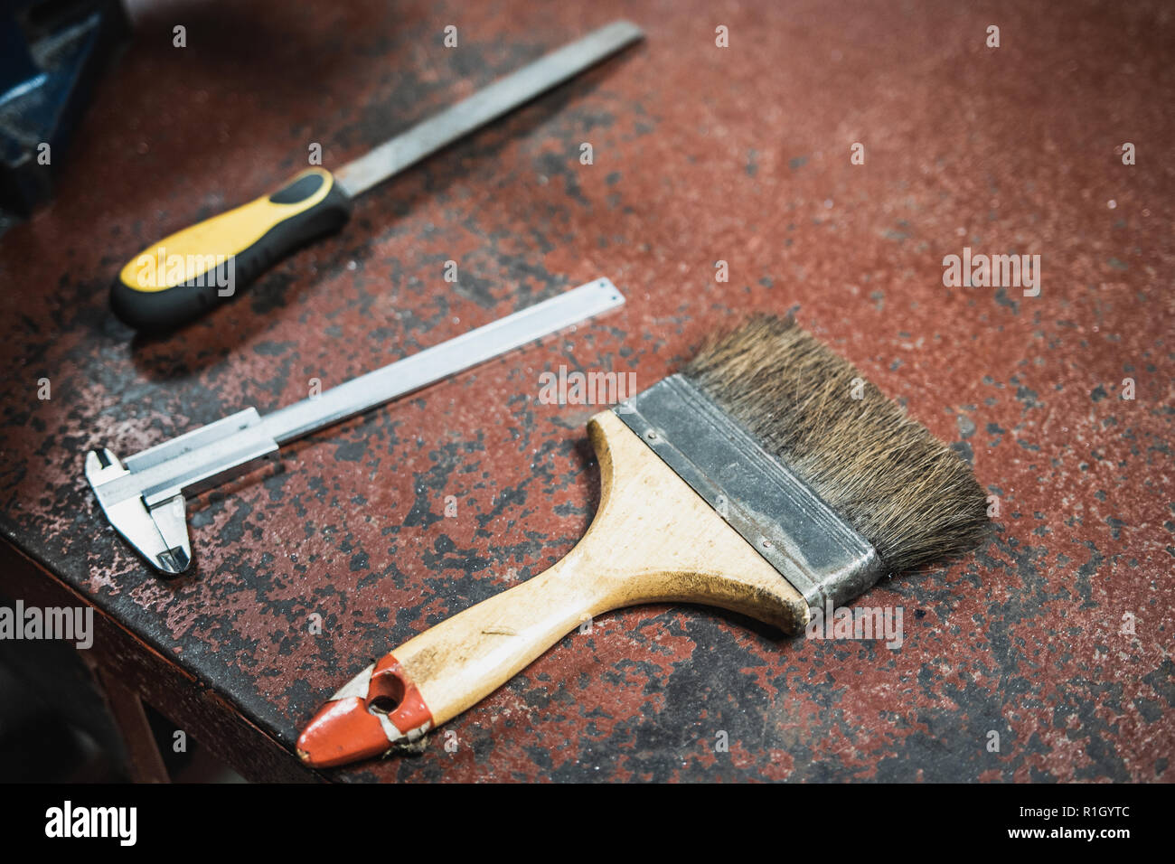 Paint brush, Vernier Caliper, and Metal file on old metallic workshop bench painted in red color - Stock Image
