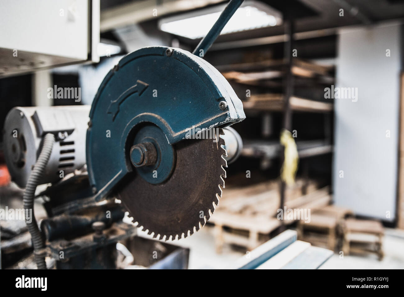 Electric saw with sharp rusted blade installed in workshop room - Stock Image