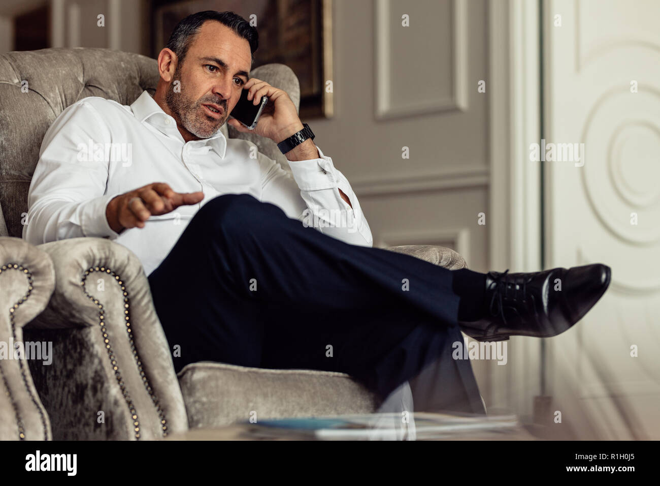 Mature traveler businessman wearing white shirt making call after arriving in the hotel room. Traveler sitting on couch and talking on smartphone. Stock Photo
