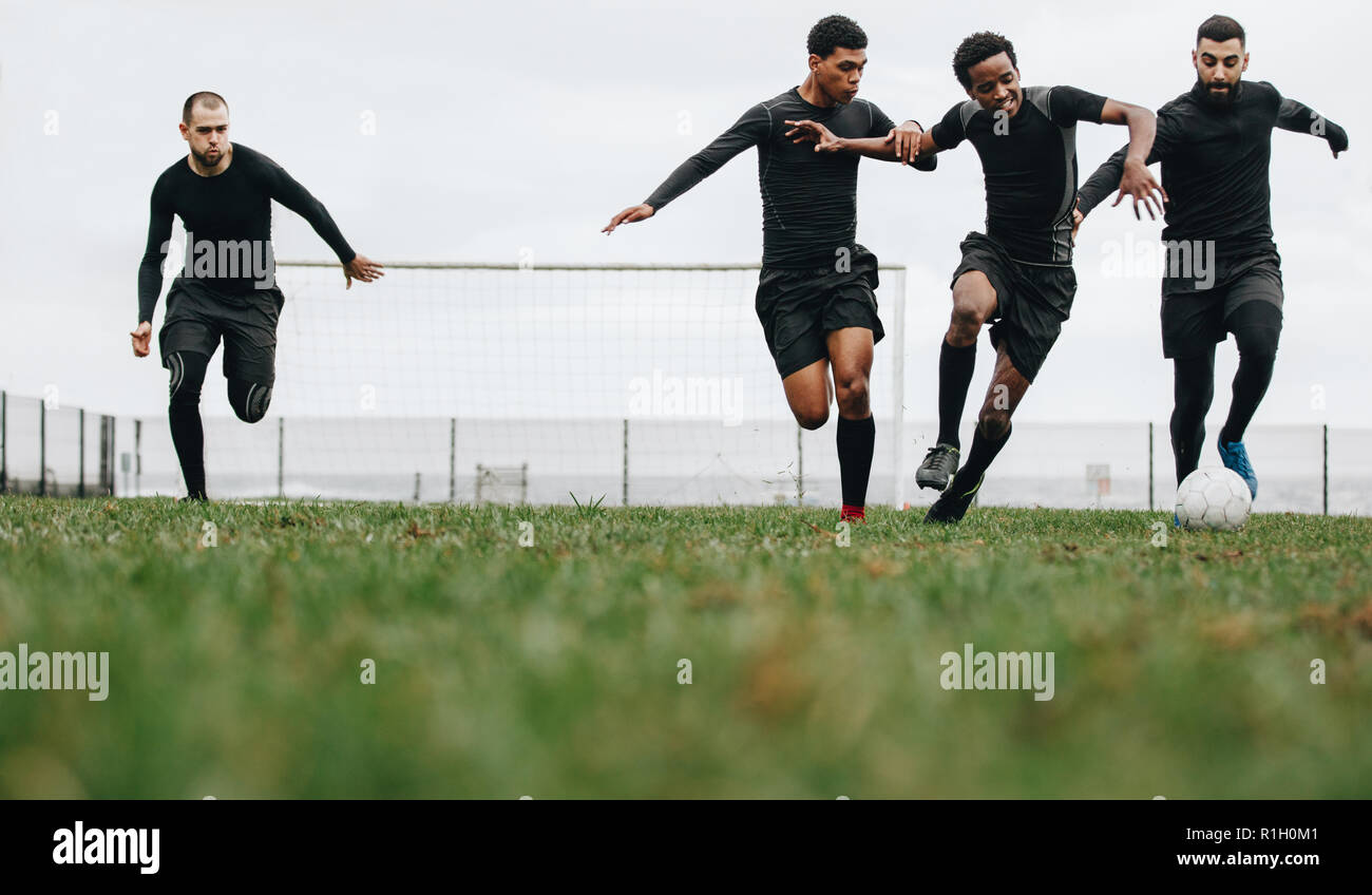 Low angle view of footballers playing on the field running for the ball. Group of men running for possession of ball while playing football. - Stock Image