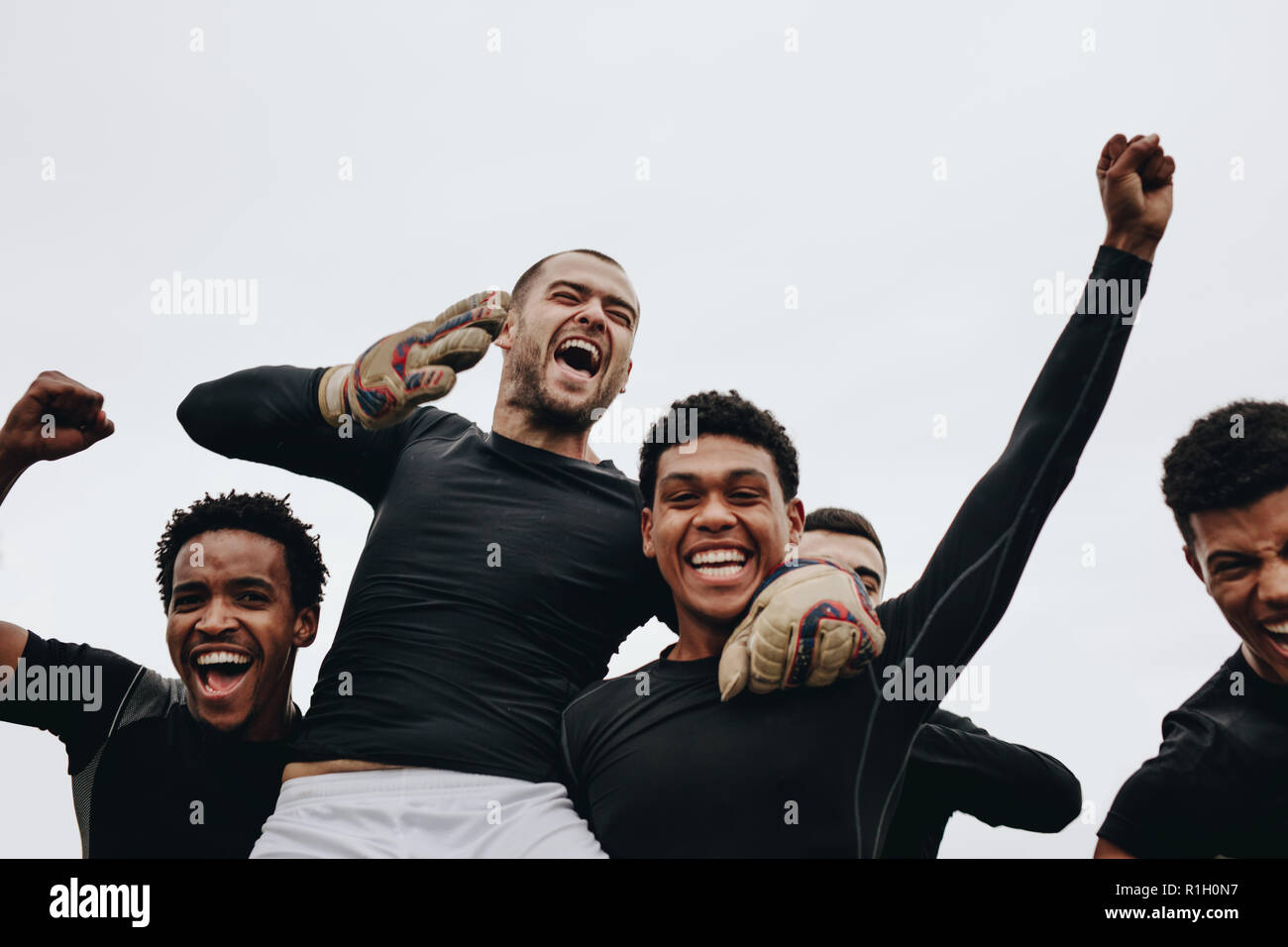 Low angle view of players carrying their teammate on shoulders celebrating success. Group of happy soccer players celebrating a win. - Stock Image