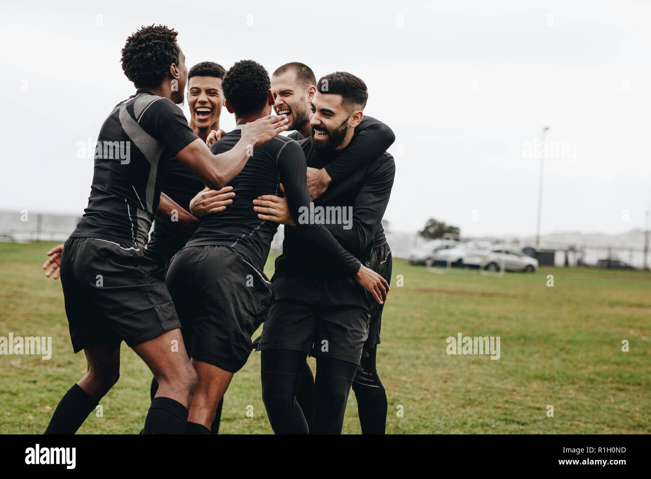 Group of football players excited on scoring a goal. Footballers coming together in a huddle celebrating victory on the field. - Stock Image