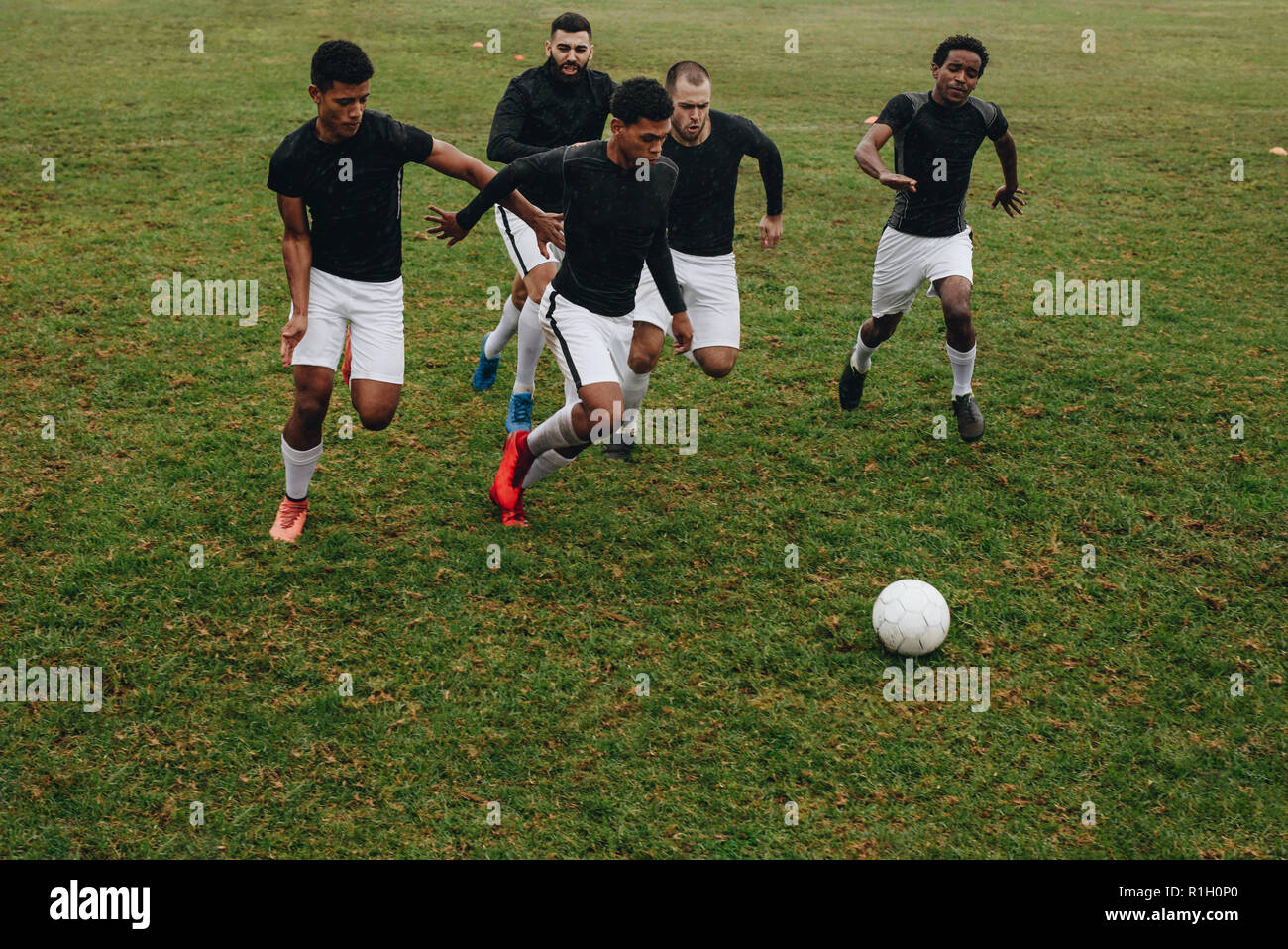 Group of men playing football on the field running for the ball. Soccer players running on field for possession of the ball. - Stock Image