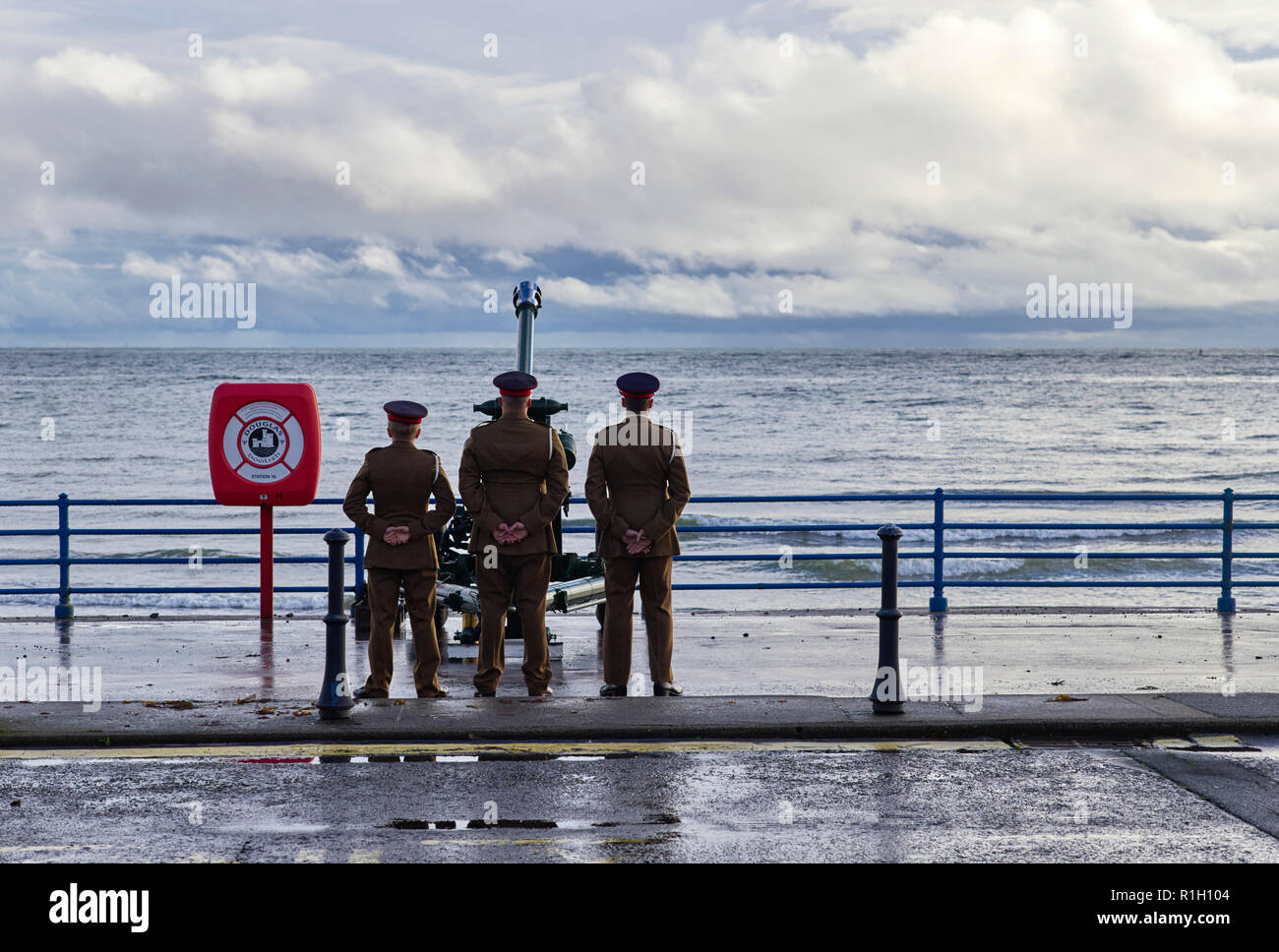 Three gunners stand behind their gun after firing blank rounds for poppy day ceremony on Douglas seafront, 2018 - Stock Image