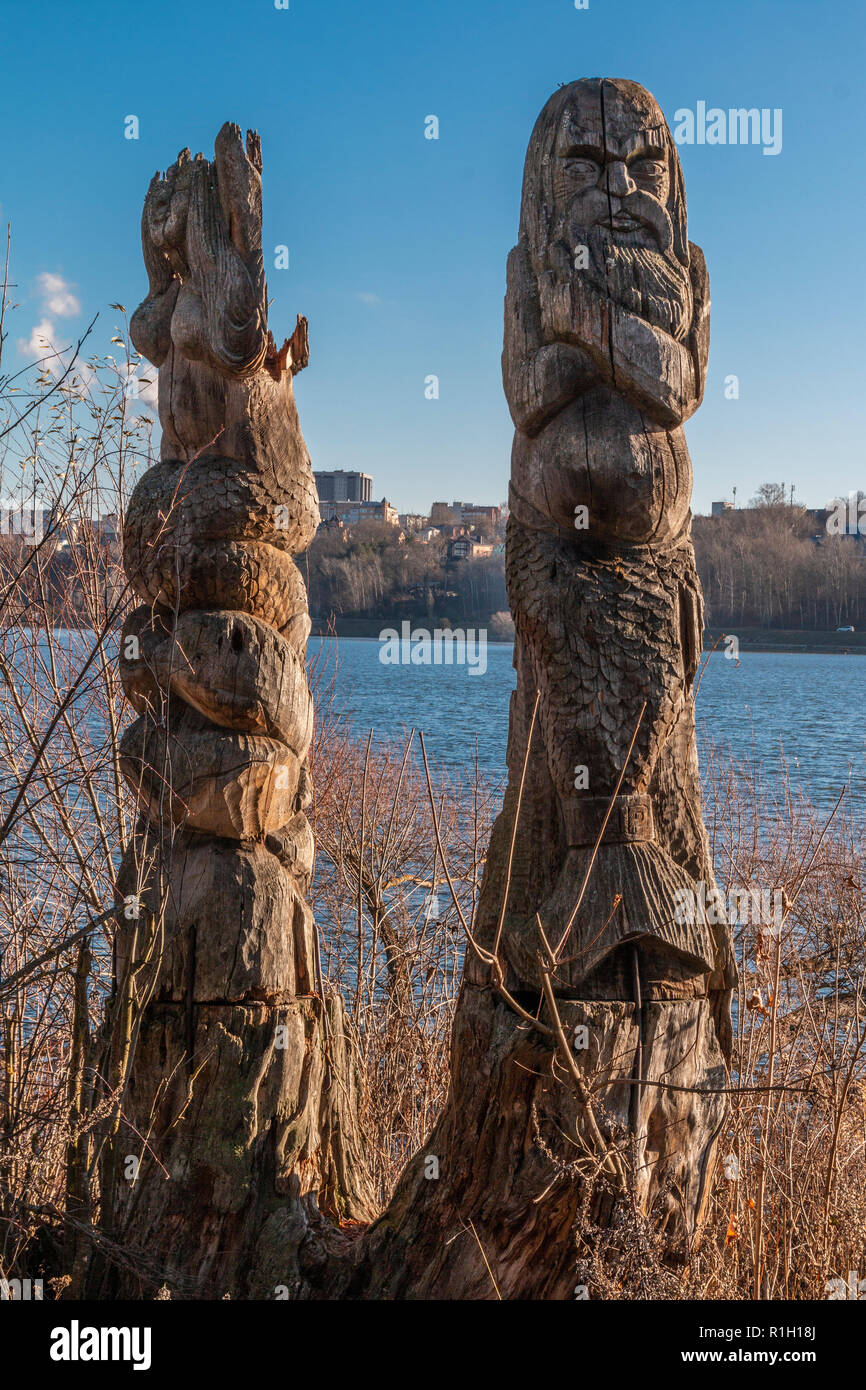 Wooden idols of the Slavic gods. Water in the background - Stock Image