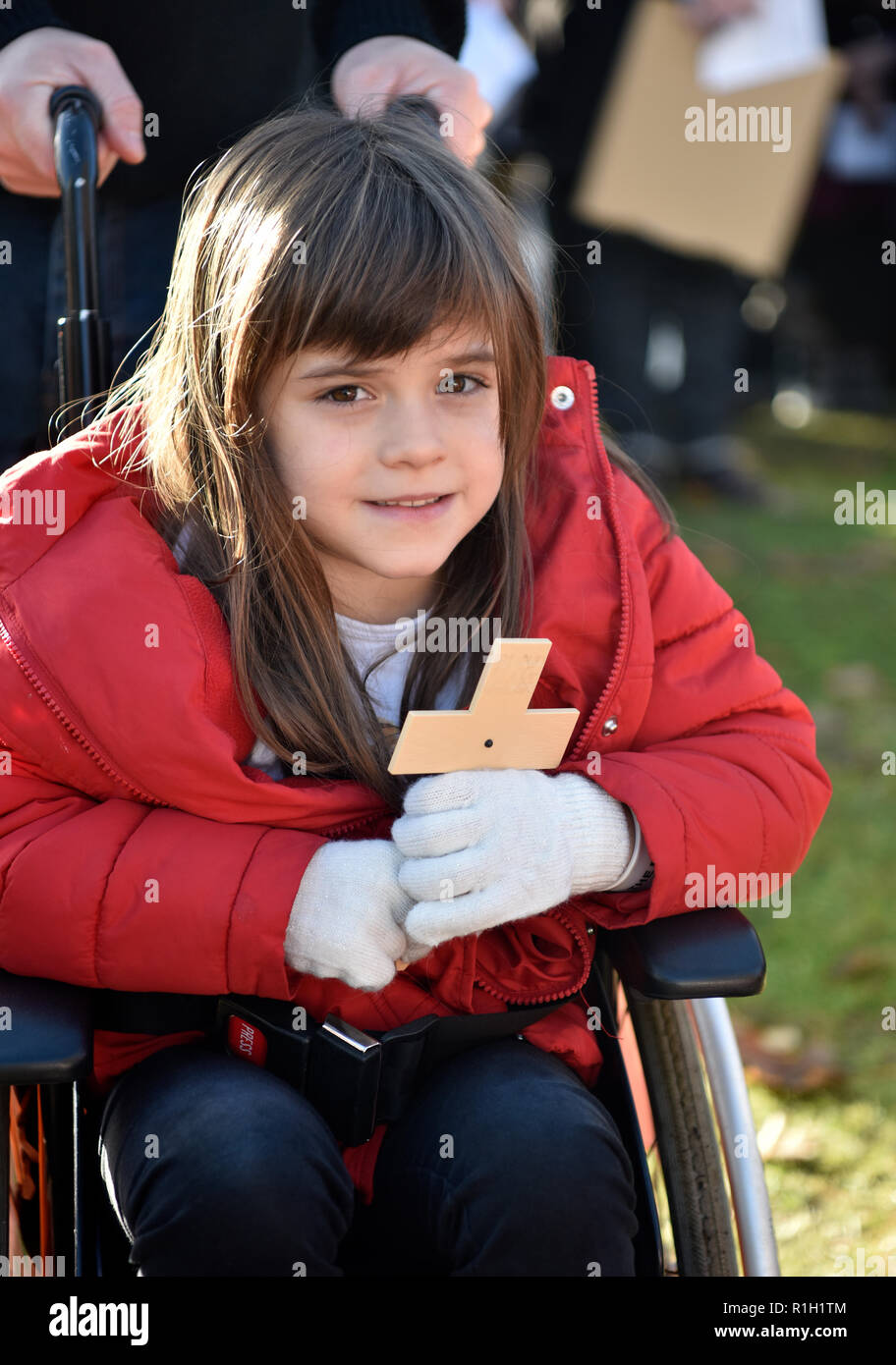 Young girl with poppy cross in wheelchair attending Remembrance Sunday, War Memorial, Bordon, Hampshire, UK. 11.11.2018. - Stock Image
