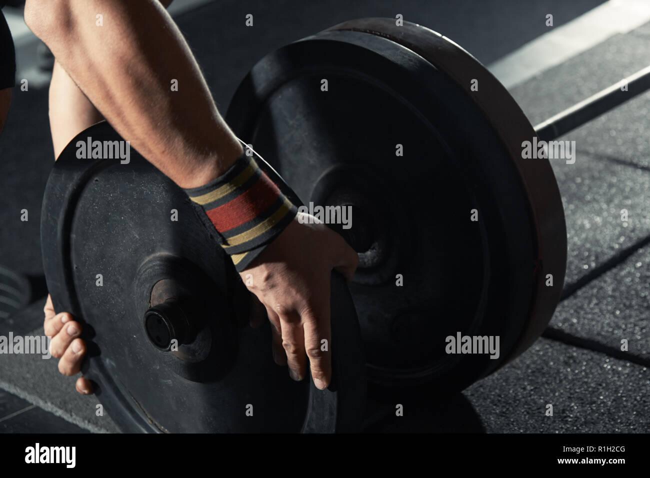 Man preparing barbell at fitness club - Stock Image