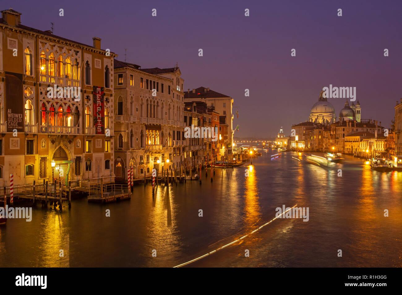 The Grand canal and the Basillica of Santa Maria della Salute viewed from Academia bridge in Venice at night - Stock Image