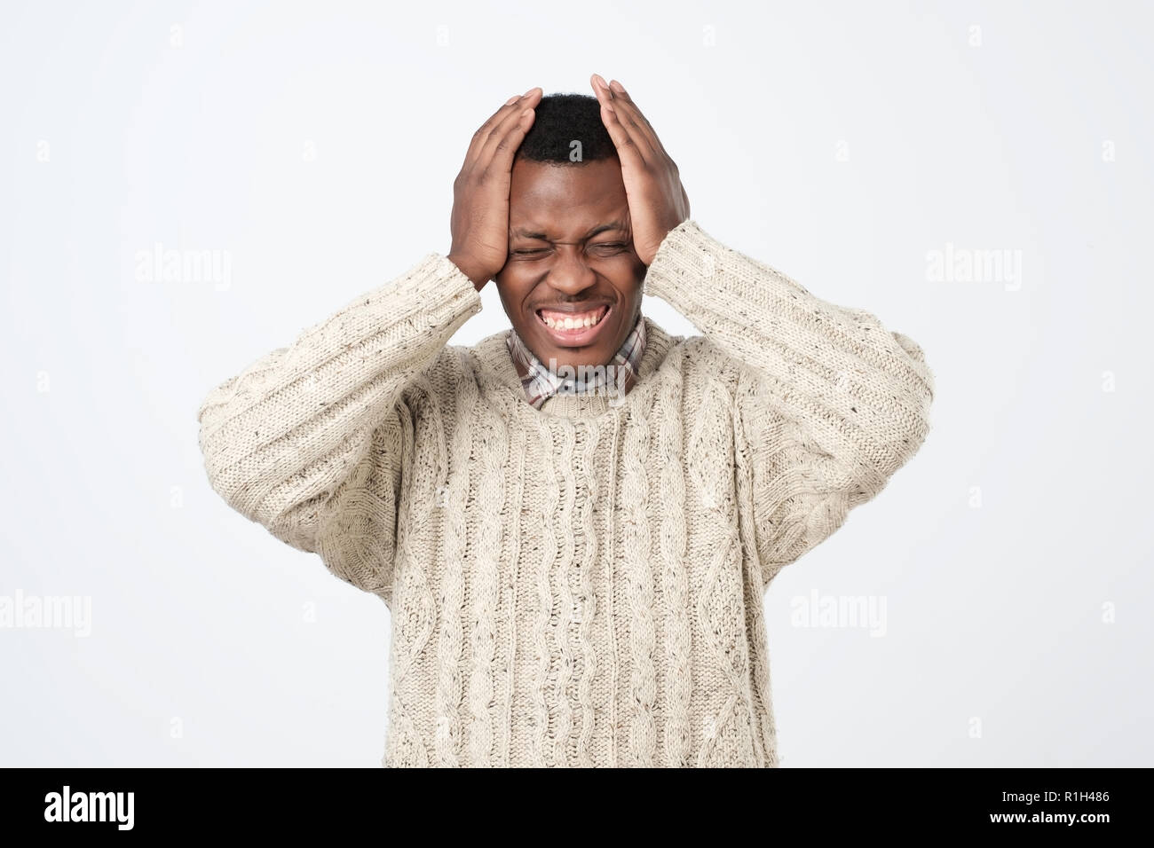Annoyed african american man in sweater in panic, shocked to hear bad news. Stressful situation concept. - Stock Image