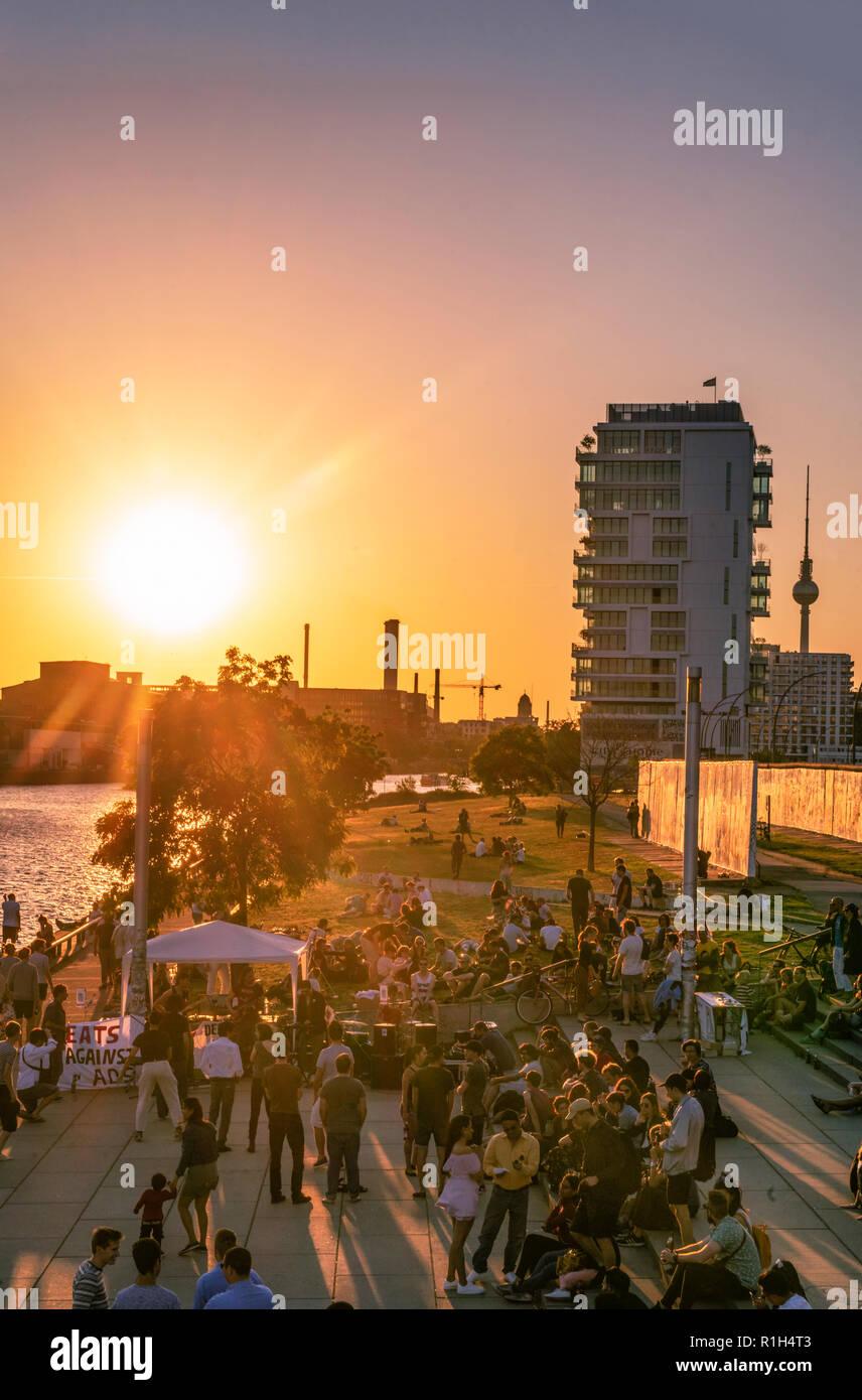 sunset at riverside Spree, Berlin wall, live band, living levels skyscraper, Friedrichshain, Berlin, Germany Stock Photo