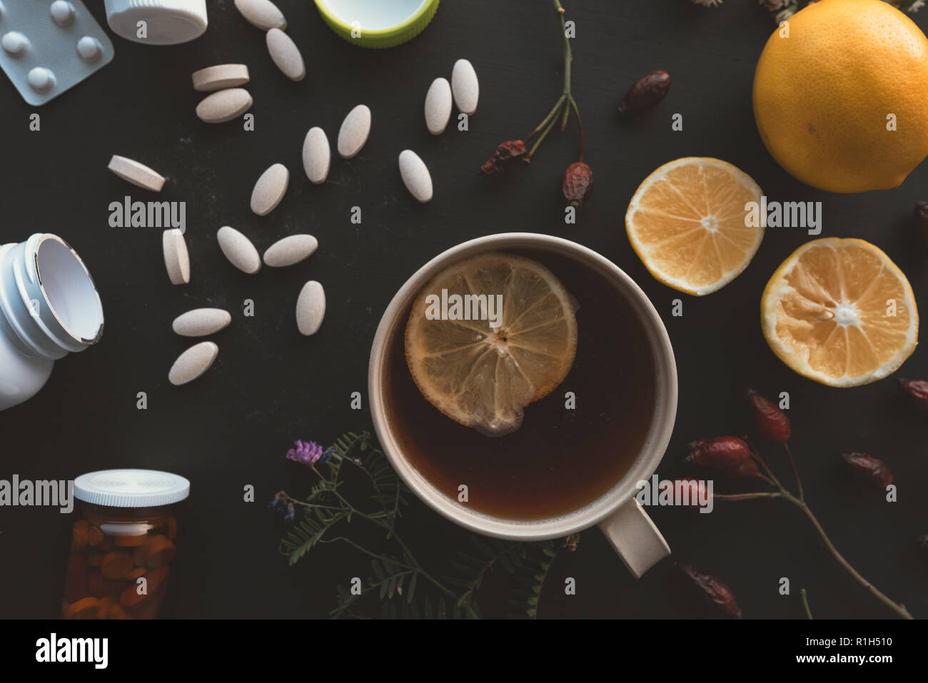 Herbal vs conventional medicine concept, cup of tea and lemon fruit or pills and medications - Stock Image