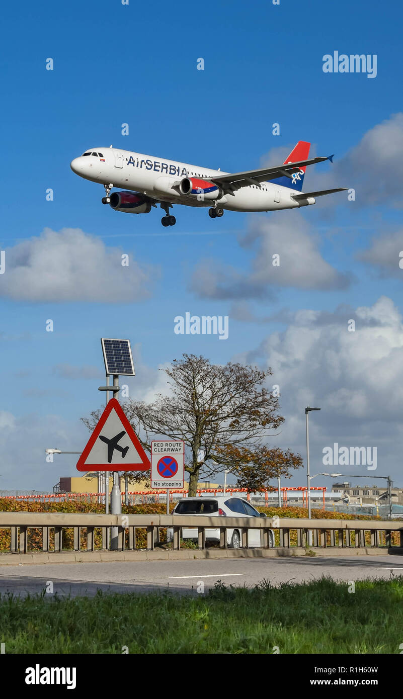 LONDON, ENGLAND - NOVEMBER 2018: Road sign on the A30 road at London Heathrow Airport warning motorists of low flying aircraft. In the background is a - Stock Image