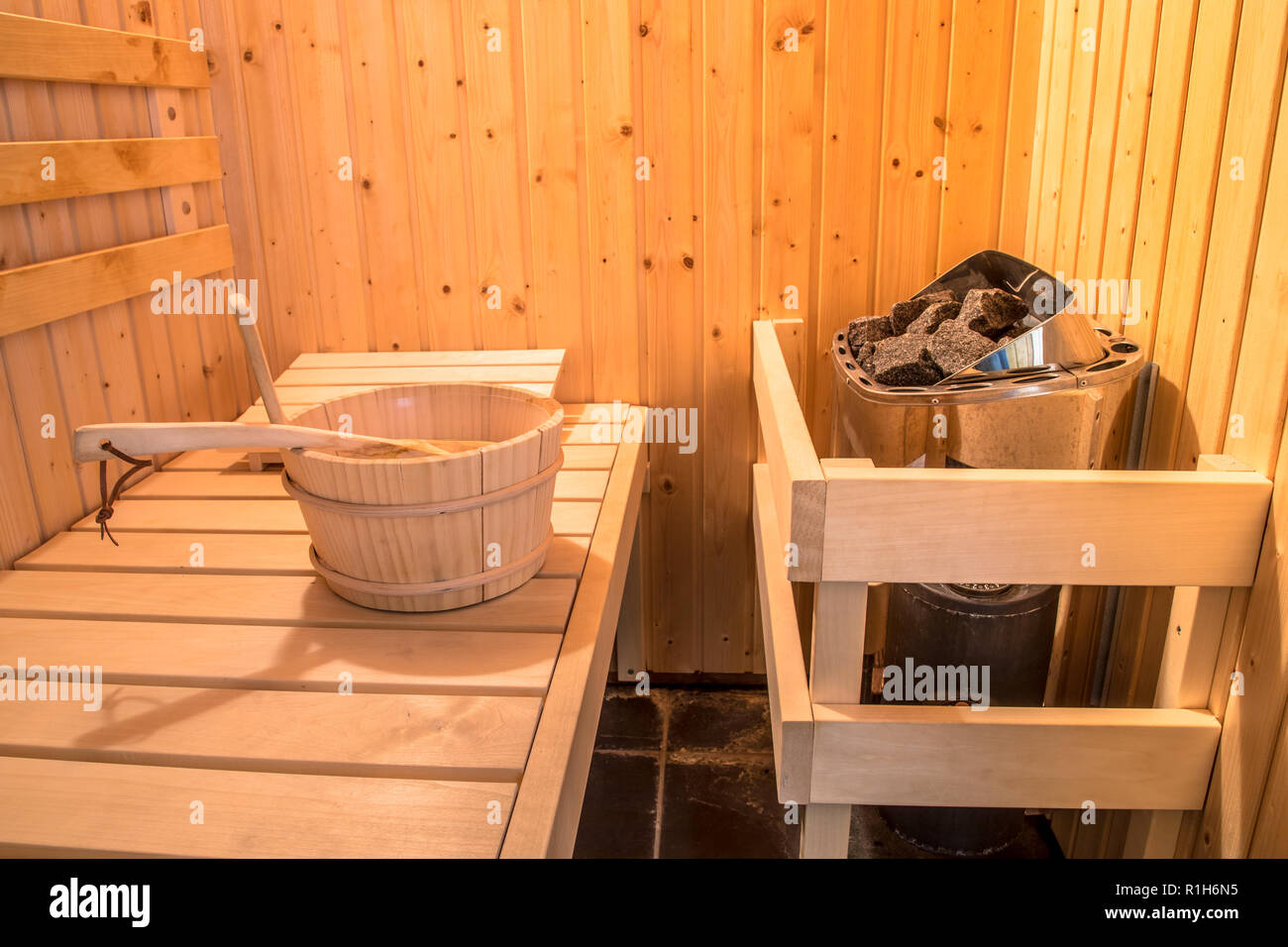 Sauna Finnish style interior with wooden bucket and seats - Stock Image