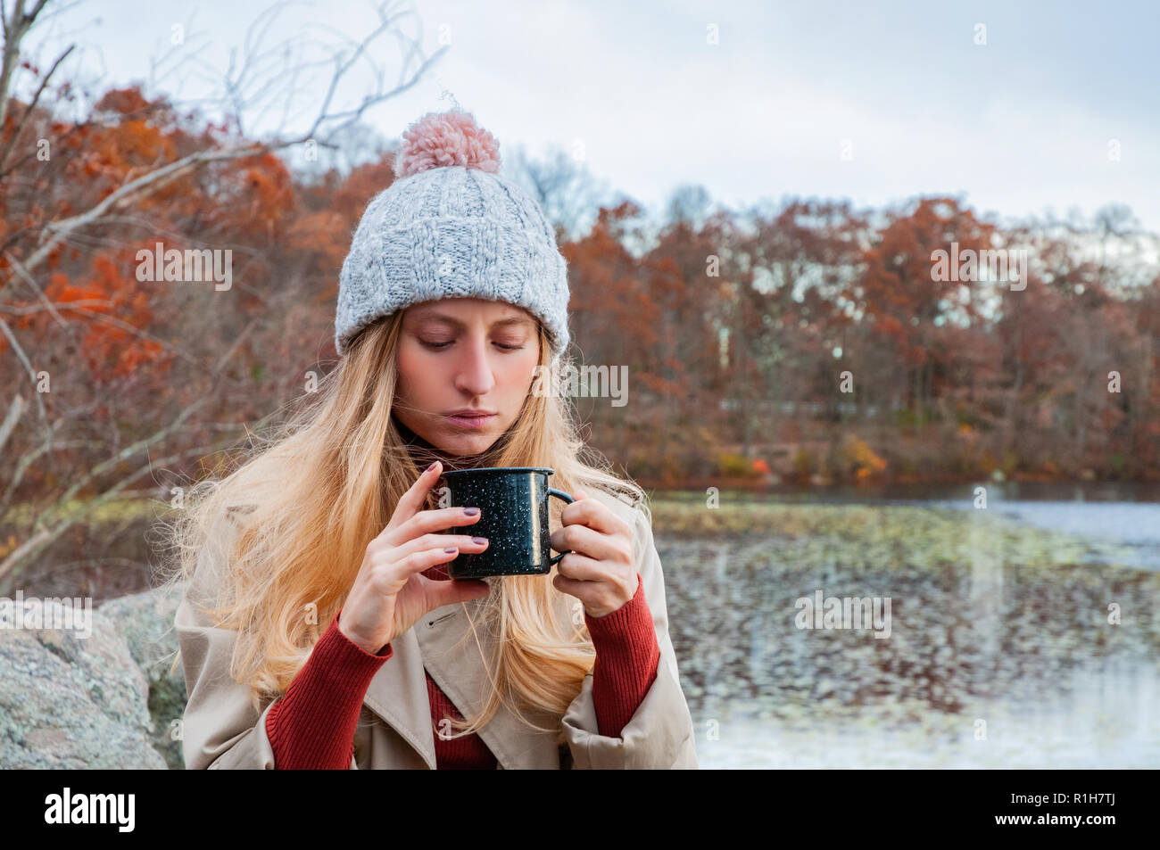 Beautiful woman in warm clothes and knitted hat drinking coffee in autumn park. Woman holding mug of coffee in the hands outdoor. Stock Photo
