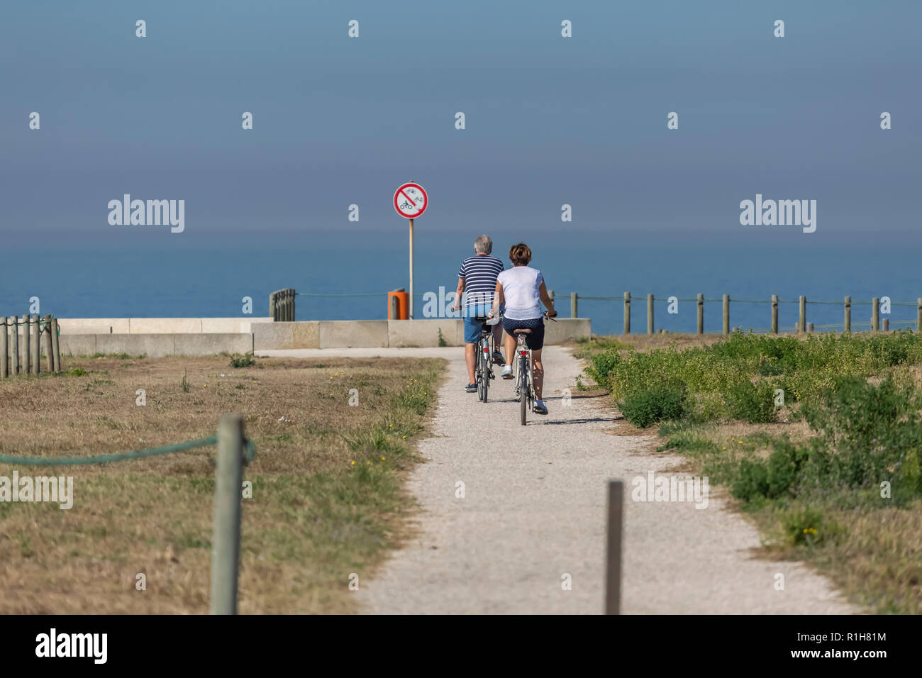 Back view of middle-aged couple, cycling on the eco pedestrian / bike path, near the sea, Portugal - Stock Image