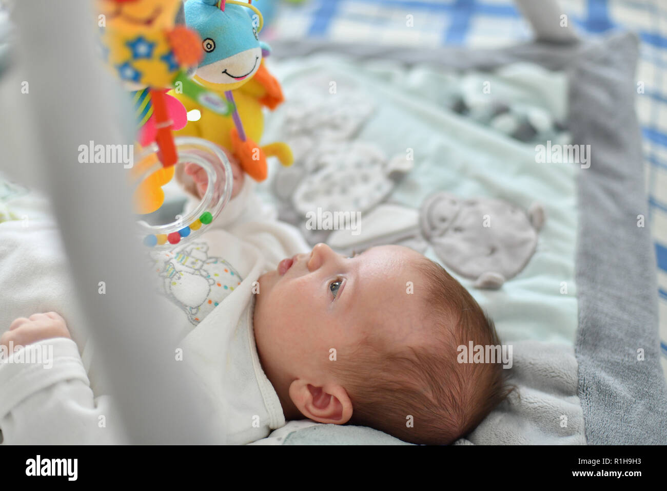 Baby boy playing with hanging toys on developing mat - Stock Image