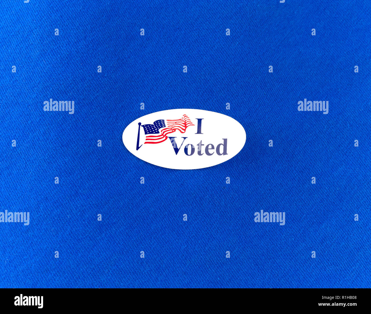 Peeling, curled election voting sticker on a blue cotton clothing shirt. - Stock Image