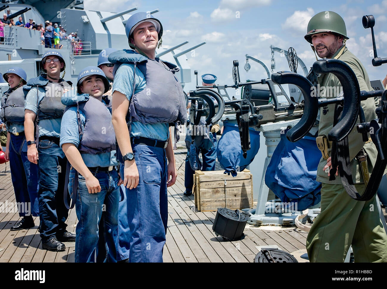 Members of the USS Alabamaís Living History Crew watch as a crowd gathers to see them engage vintage aircraft in a mock World War II battle, Aug. 12,  Stock Photo