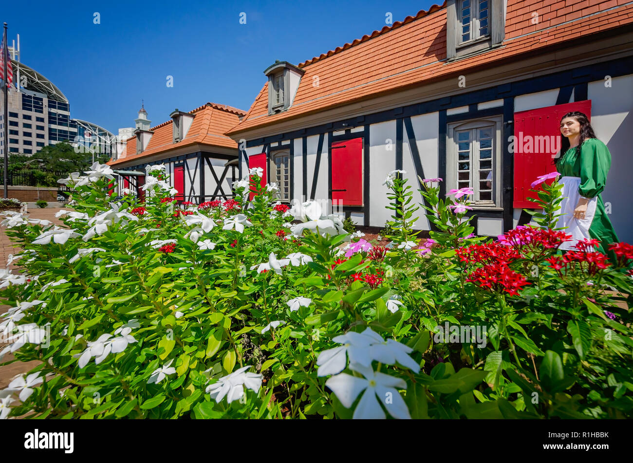 A volunteer stands beside a bed of vinca in the courtyard of the Fort of Colonial Mobile, Aug. 24, 2017, in Mobile, Ala. - Stock Image