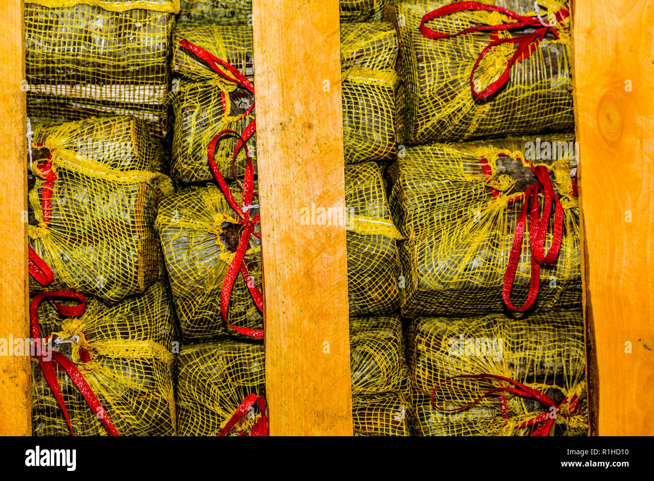 firewood logs cut and placed inside yellow sacks and tied with a red ribbon placed in a wooden container - Stock Image
