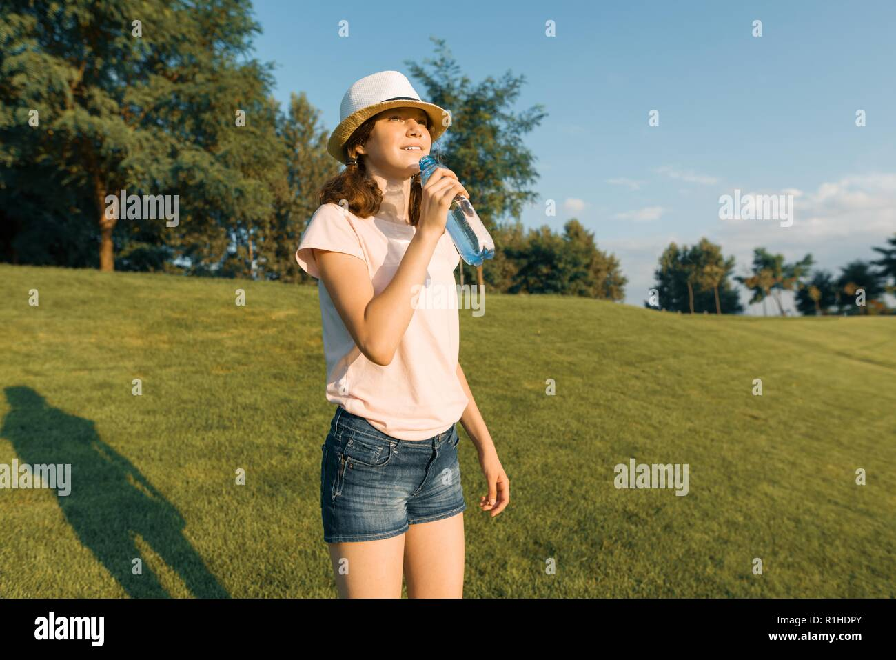 Young teenager girl drinks refreshing water from a bottle on a hot summer day, walking in the park, the golden hour. - Stock Image
