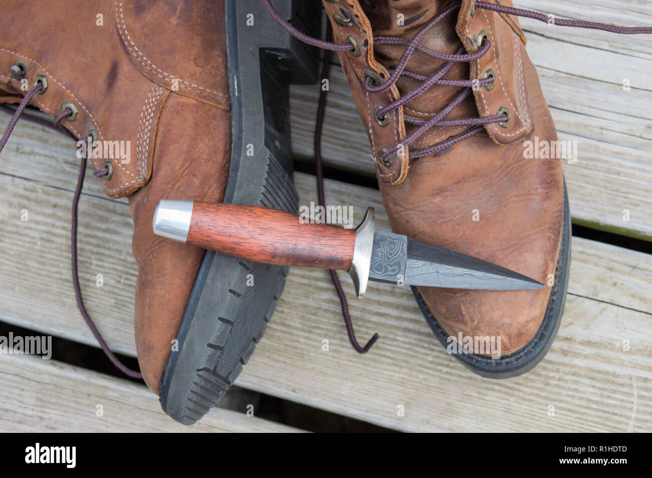 A boot knife displayed on work boots. - Stock Image
