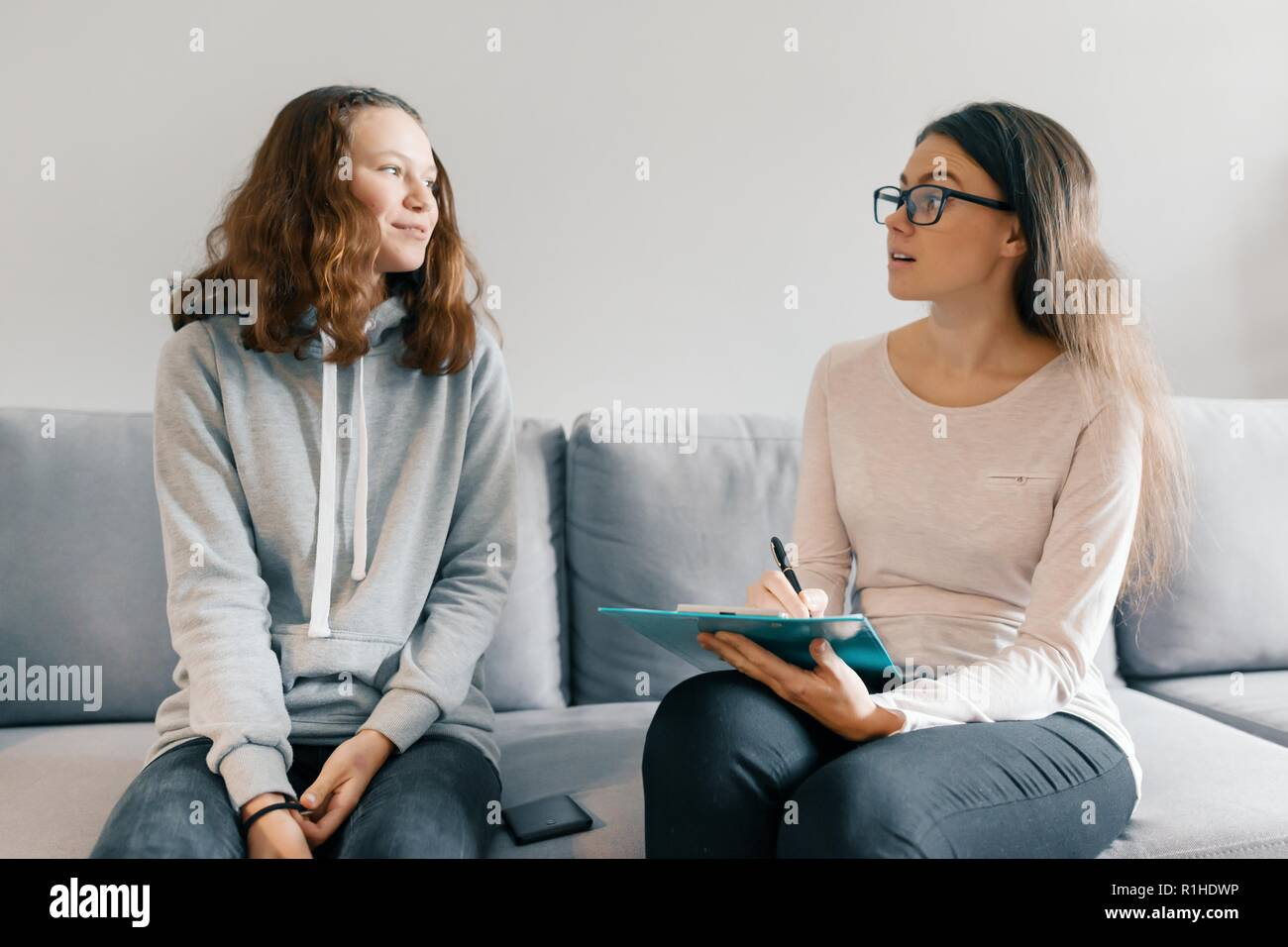 Teenager patient girl talking with professional psychotherapist in office Stock Photo