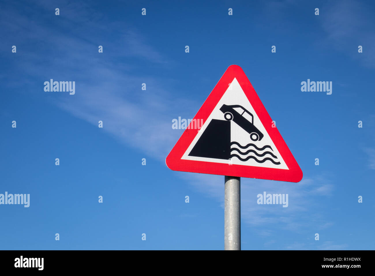Highway code red triangle road sign in the United Kingdom warning motorists about the danger of a quayside or river bank. - Stock Image
