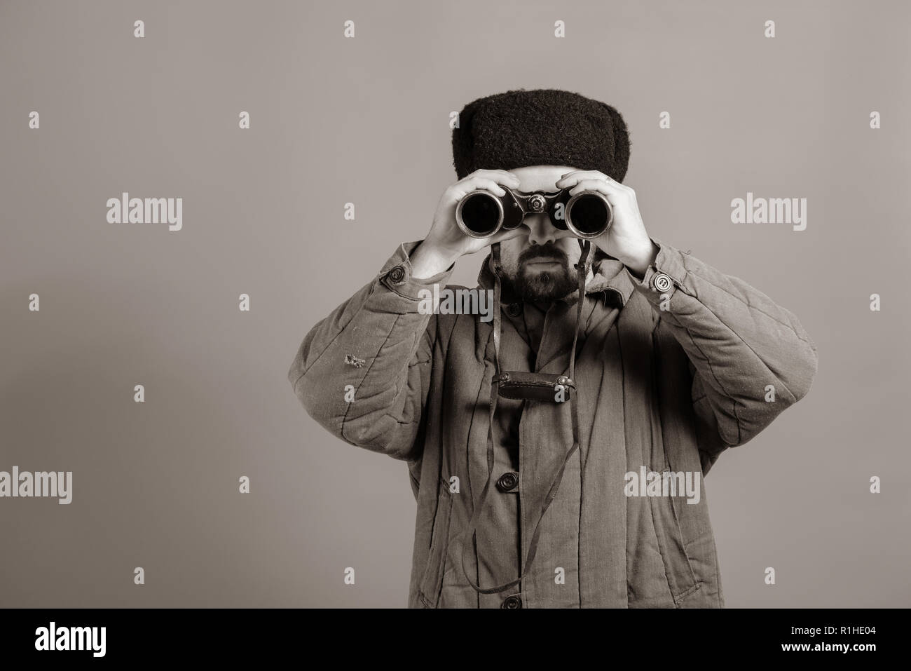Conception - soldier on the post. Observation with binoculars, uniforms of the Great Patriotic War, sepia effect Stock Photo