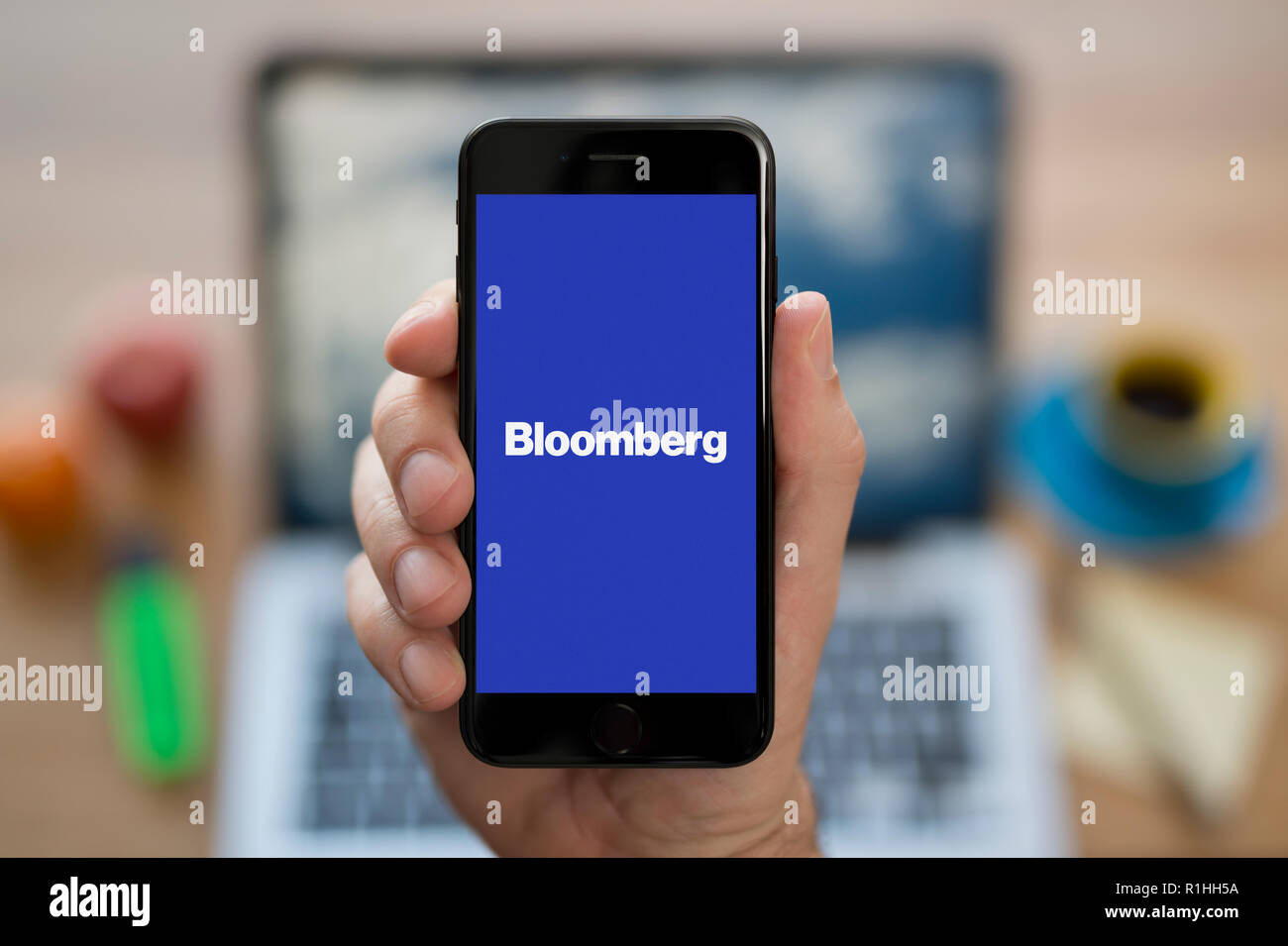 A man looks at his iPhone which displays the Bloomberg logo, while sat at his computer desk (Editorial use only). - Stock Image