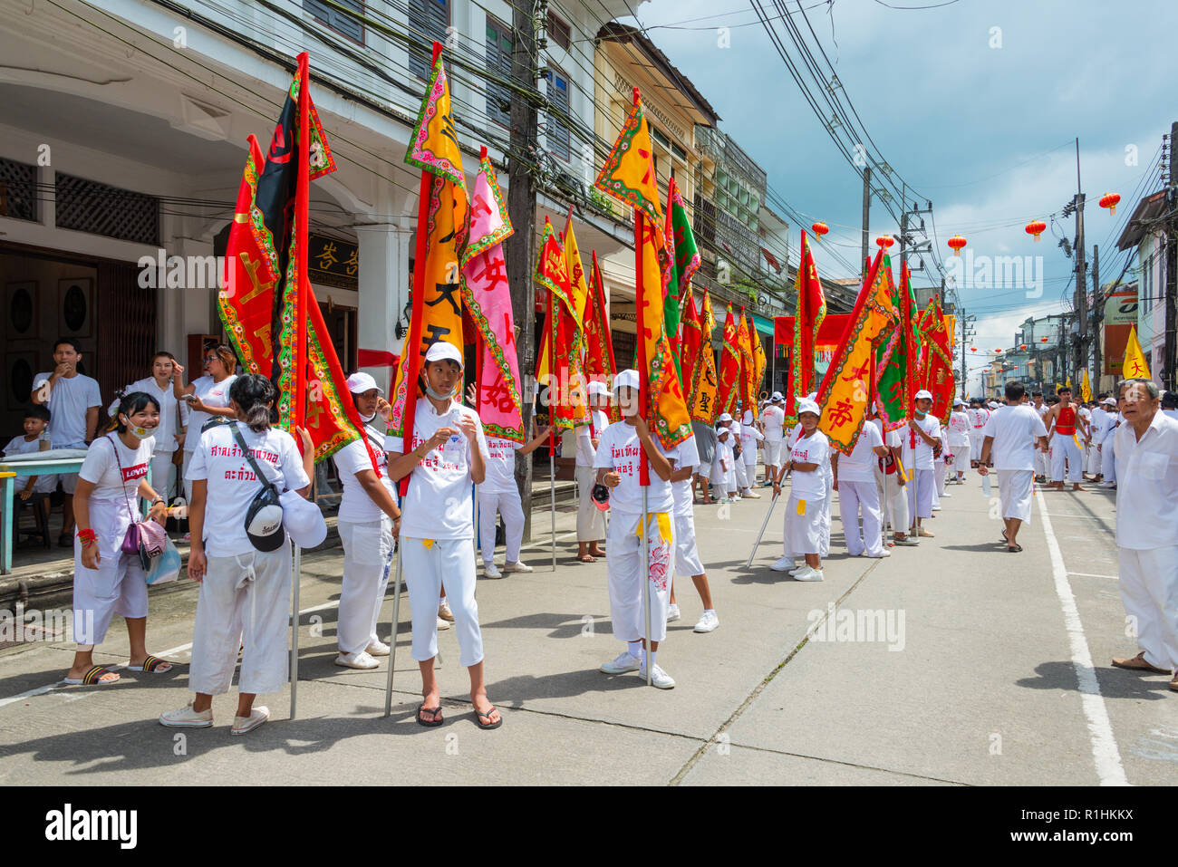 Phang Nga, Thailand - October 14, 2018: People in white dress holding flags marching on street in vegetarian festival parade in Phang Nga, Thailand - Stock Image