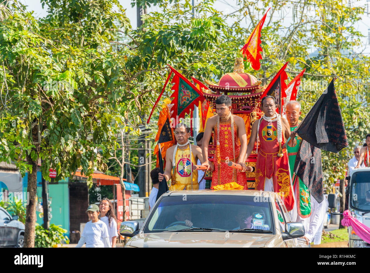 Phang Nga, Thailand - October 15, 2018: People in Chinese costume on back of pickup car act as assumed Chinese god marching on street in vegetarian fe - Stock Image