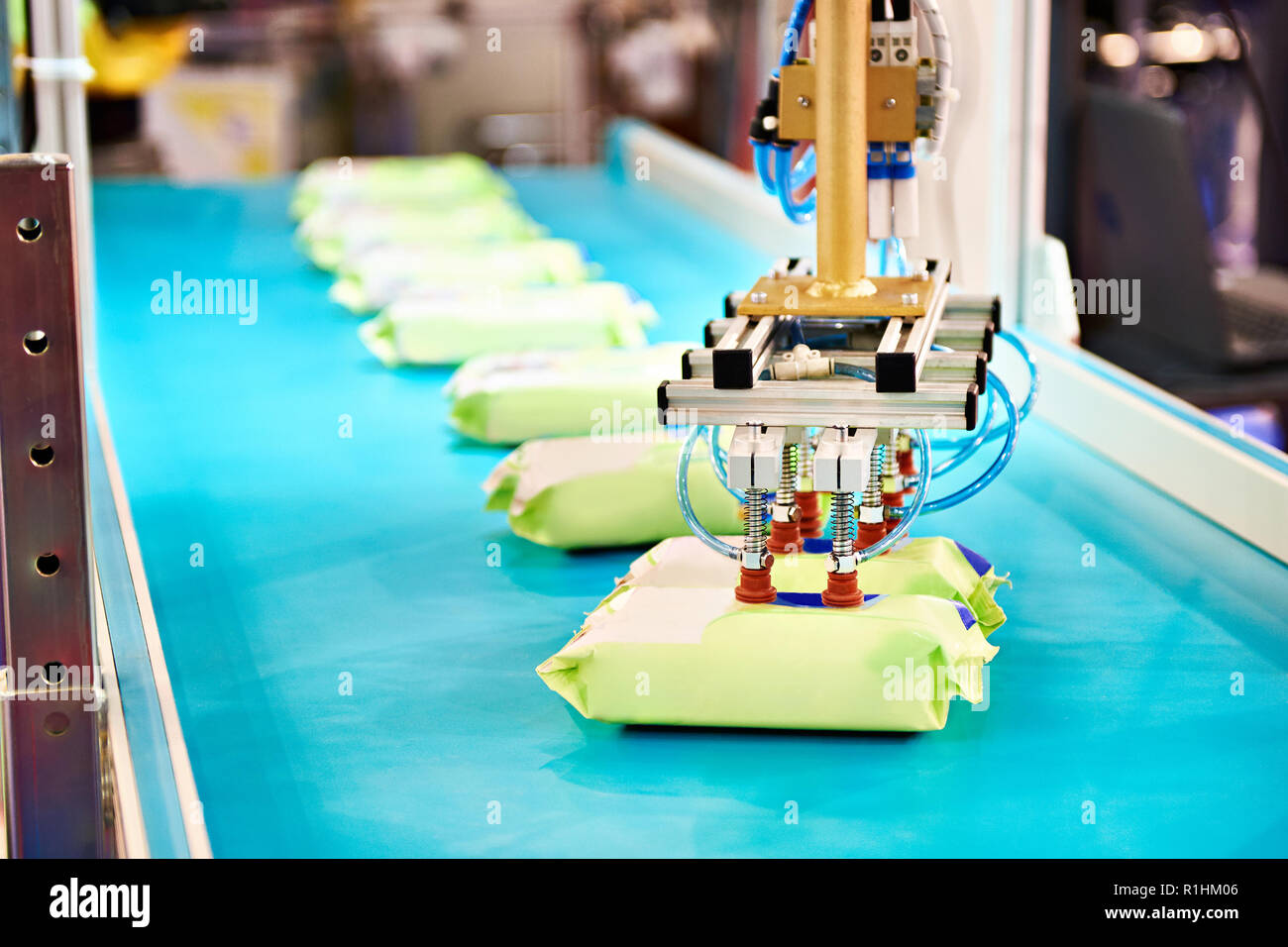 Hand robot manipulator for packaging products on conveyor - Stock Image
