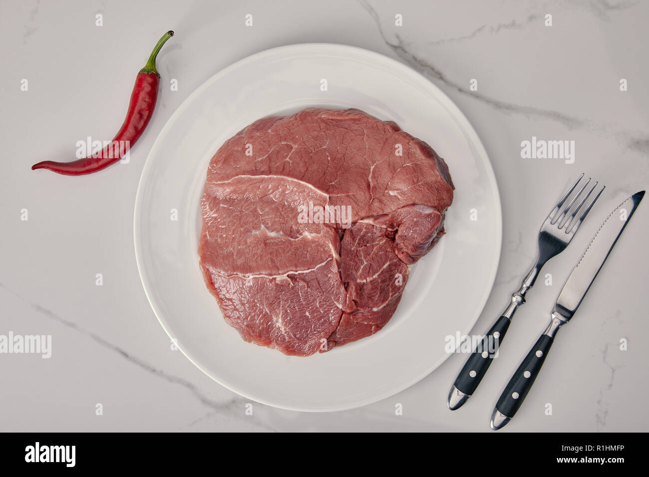 top view of fresh raw meat on plate with kitchen cutlery and chilli pepper on white background - Stock Image
