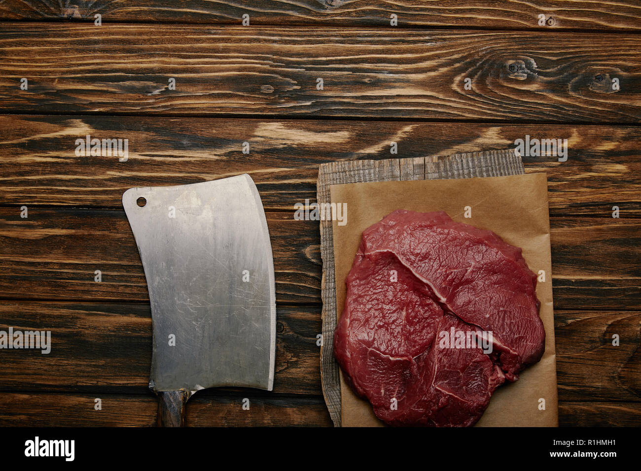 top view of raw meat on baking paper with butcher knife on wooden background Stock Photo