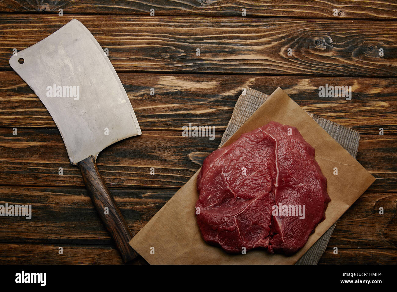 top view of raw meat on baking paper with butcher knife on wooden background - Stock Image