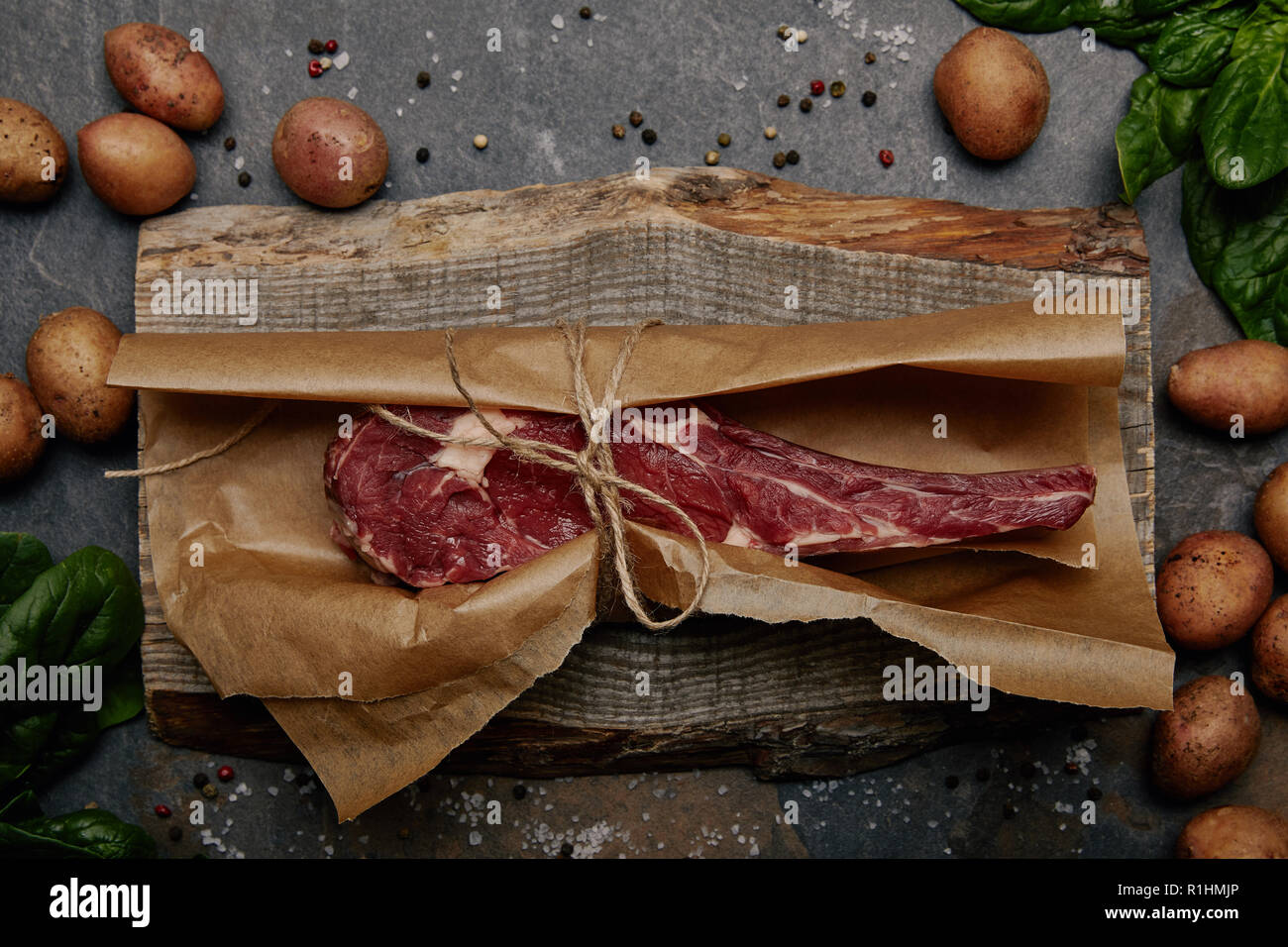 raw rib eye steak wrapped in baking paper on wooden board with spices and potatoes - Stock Image