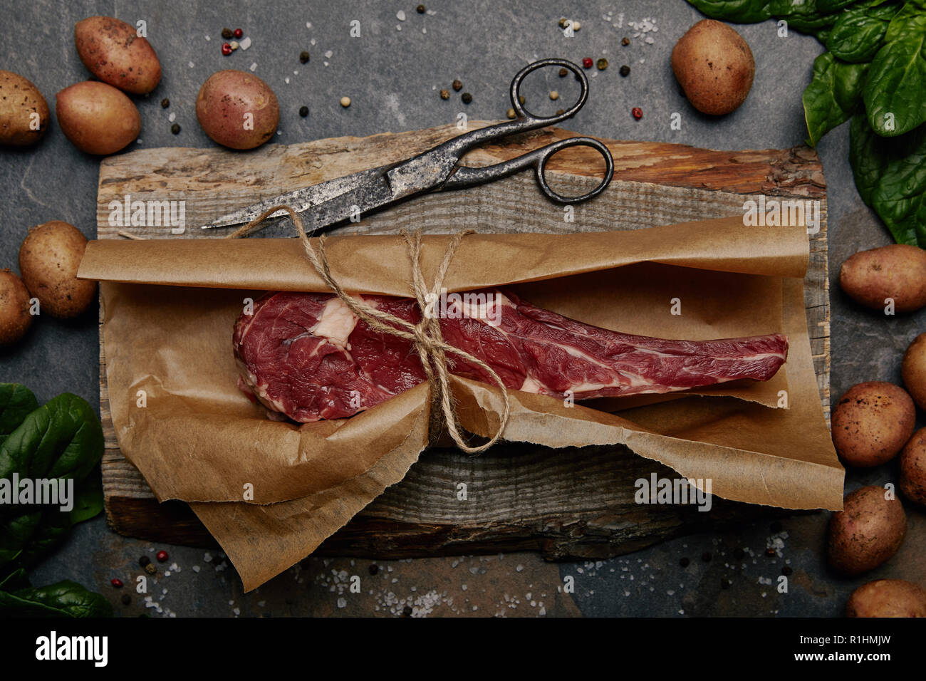 top view of raw rib eye steak wrapped in baking paper on wooden board with spices and potatoes - Stock Image