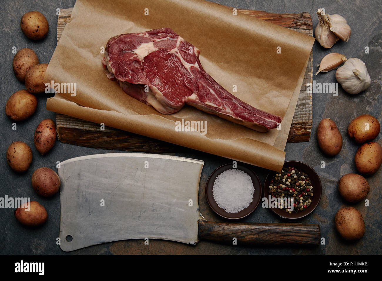 flat lay with raw rib eye steak on baking paper with butcher knife, spices, potatoes and garlic - Stock Image