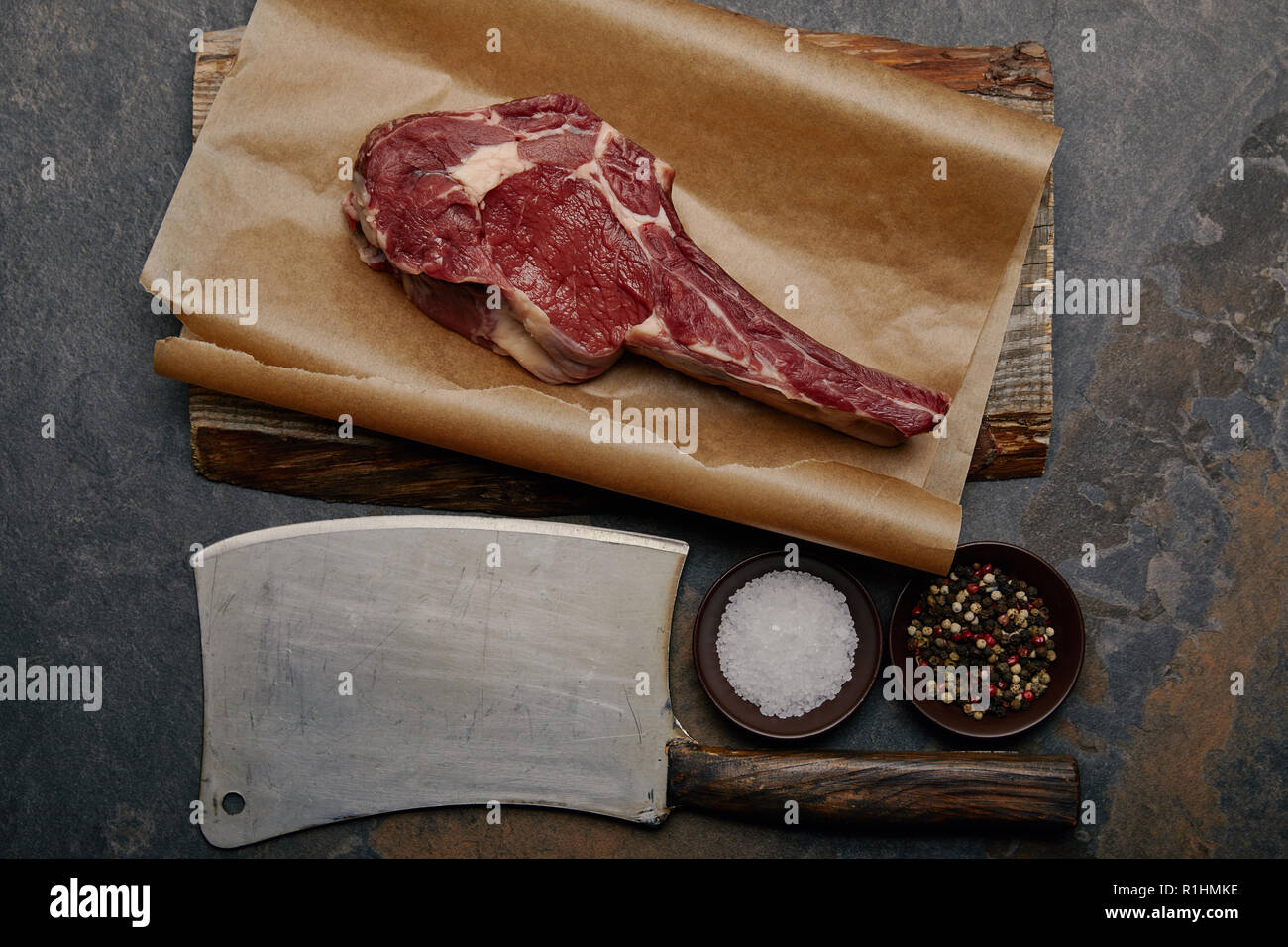 top view of raw rib eye steak on baking paper with butcher knife, spices Stock Photo