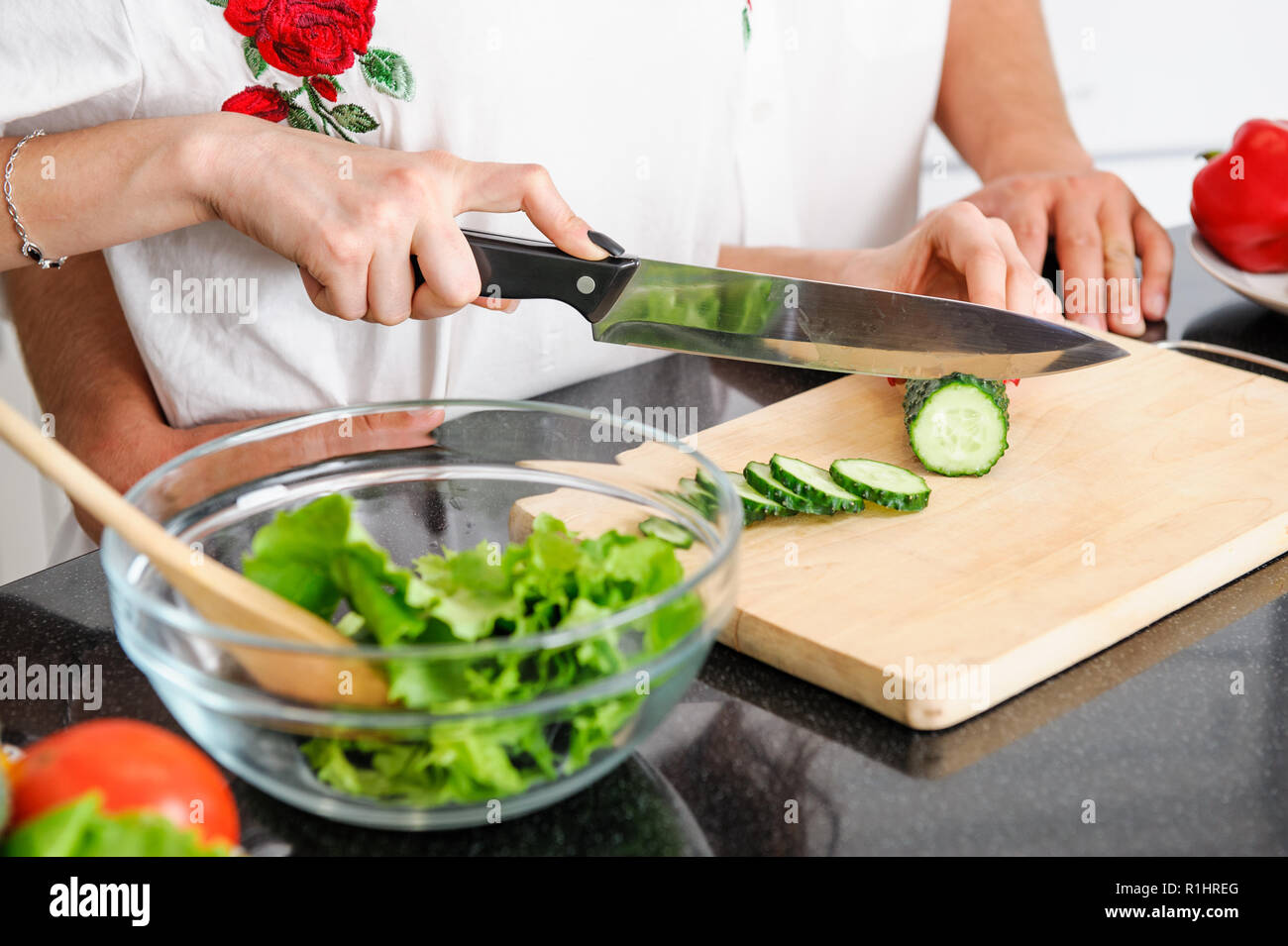 young man and woman hands cooking healthy vegetarian food from fresh vegetables - Stock Image
