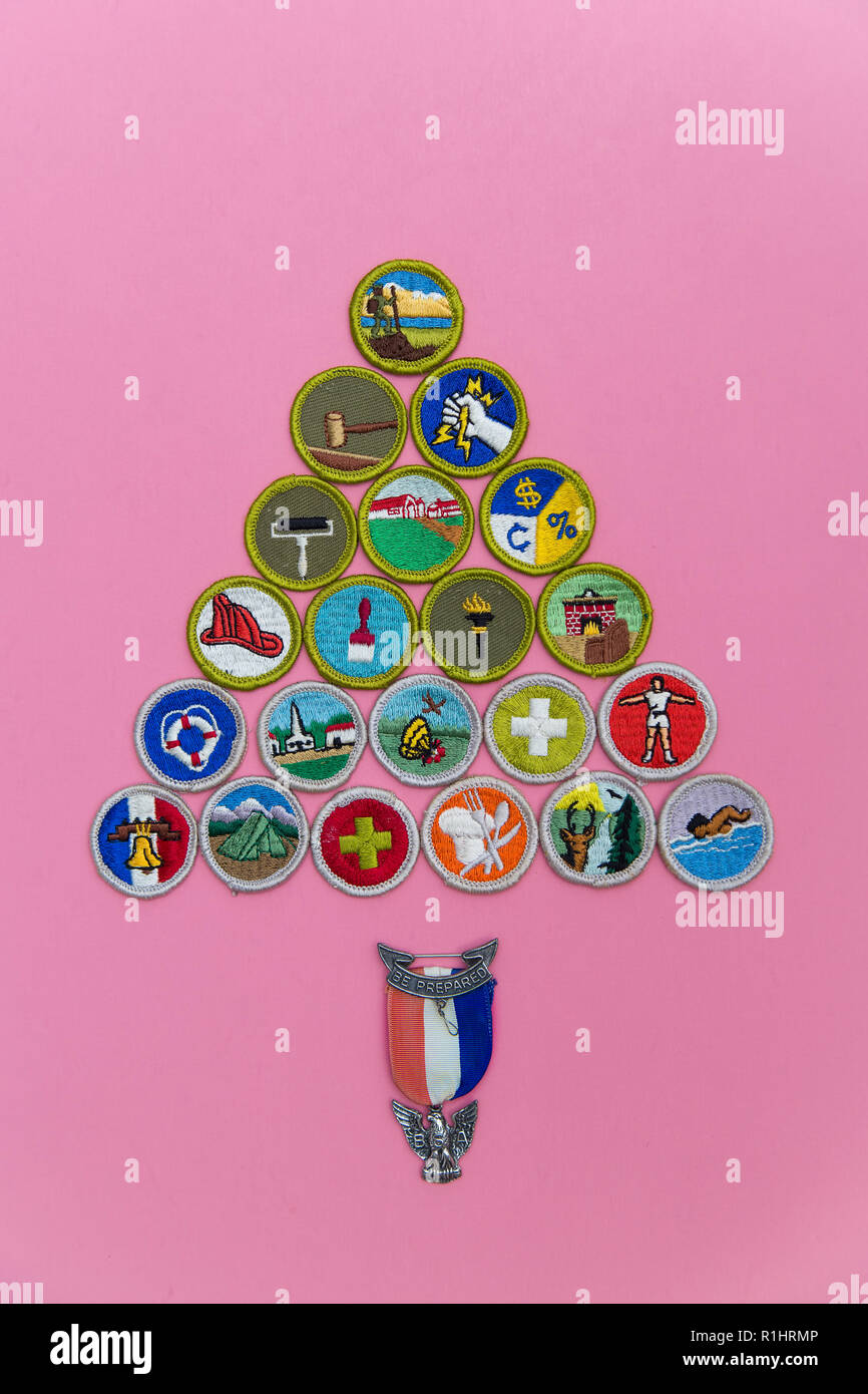 SAINT LOUIS, UNITED STATES - AUG 22, 2018:  A geometric arrangement of Boy Scouts of America (BSA) merit badges with Eagle pin on pink background as B - Stock Image