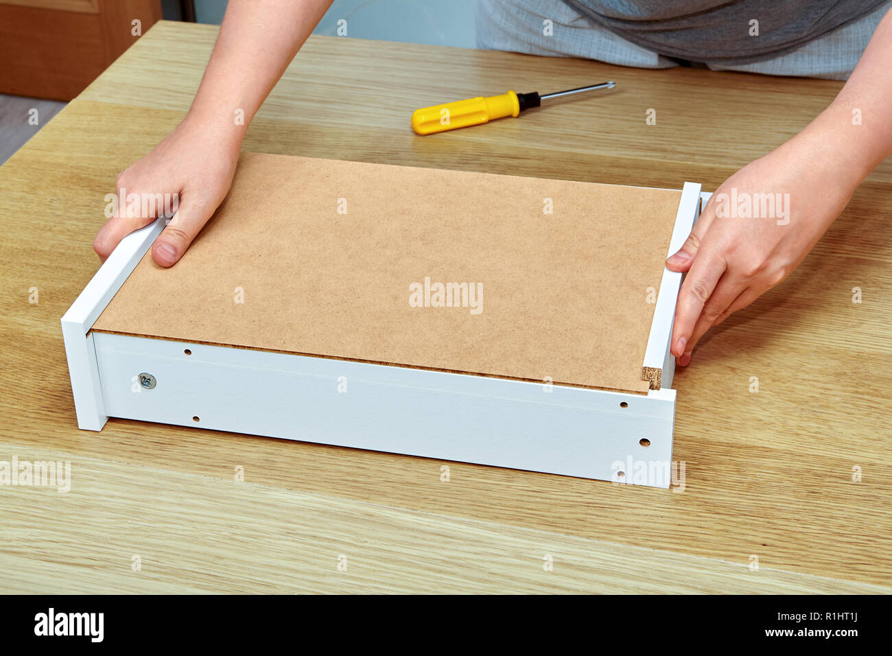 The Handyman Puts Together Two Parts Of A Wooden Drawer Made Of