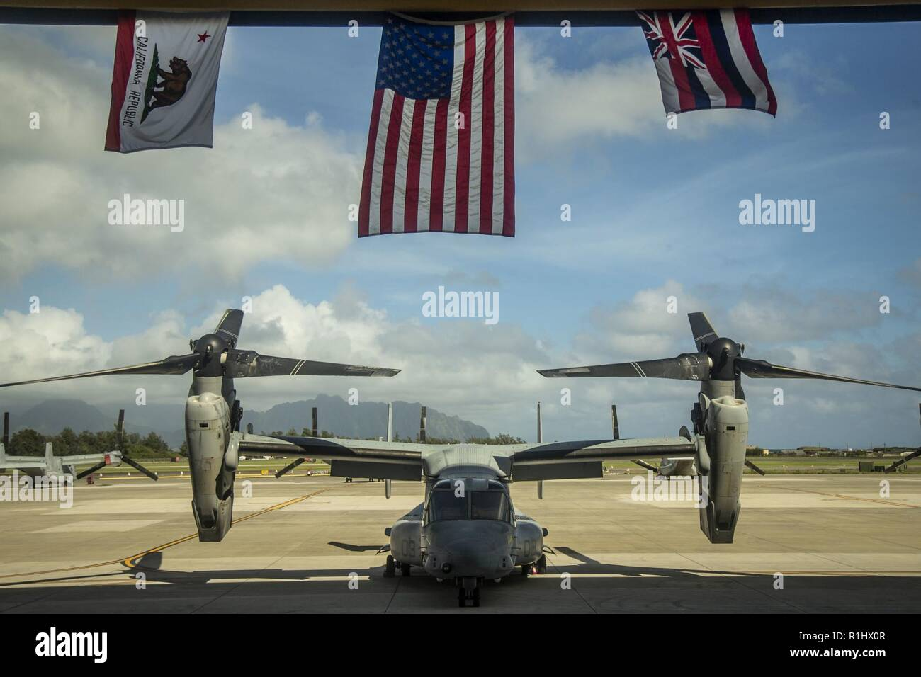 A static display of an MV-22B Osprey is showcased under the United States flag, flanked by the California and Hawaii state flags, symoblozing  Marine Tiltrotor Squadron (VMM) 363's journey during the squadron's hangar dedication ceremony, Marine Corps Air Station Kaneohe Bay, Marine Corps Base Hawaii, Sept. 21, 2018. The dedication ceremony celebrated the arrival of Marines with VMM 363 and everyone that assisted in the construction of the hangar. The arrival of a second MV-22B Osprey squadron significantly increases Marine Aircraft Group 24's capability to respond to local emergencies within  Stock Photo