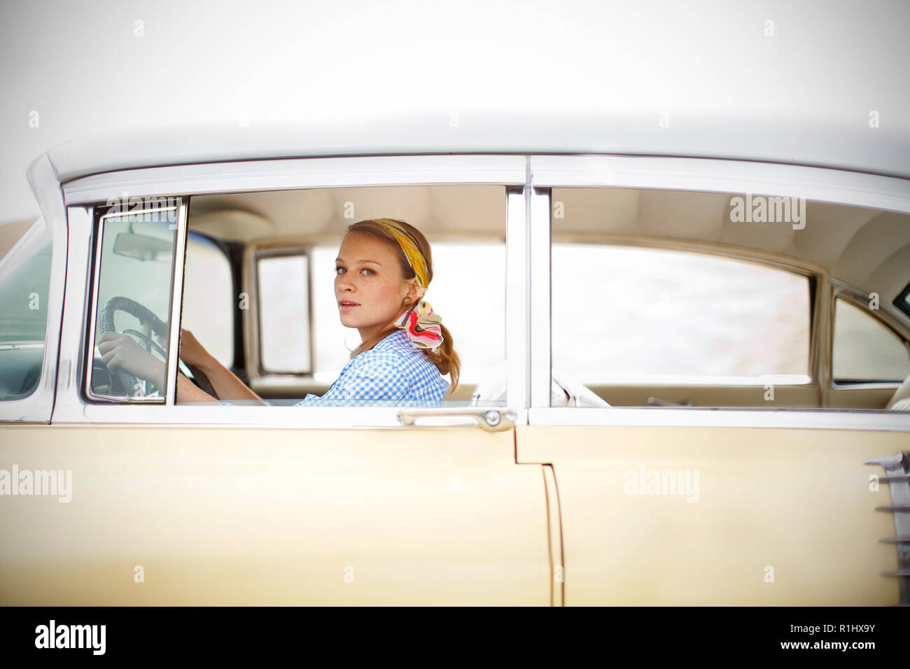 Young woman in 1950s outfit driving a vintage car Stock Photo