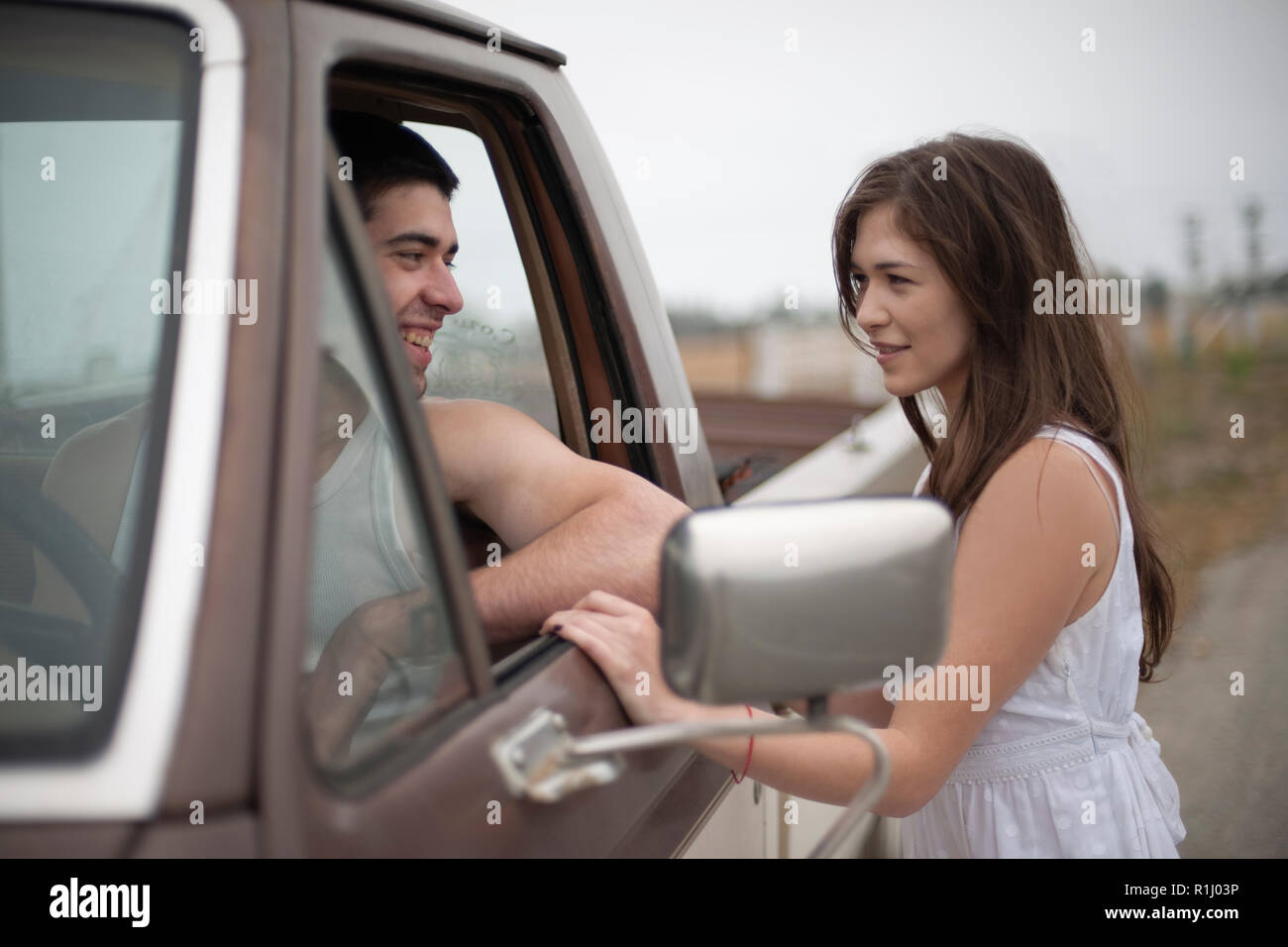 Young couple talking to each other through a car window - Stock Image