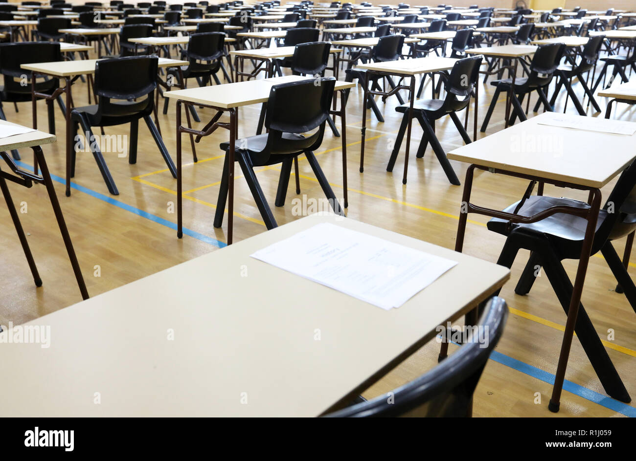 View of large exam room hall and examination desks tables lined up in rows ready for students at a high school to come and sit their exams tests paper - Stock Image